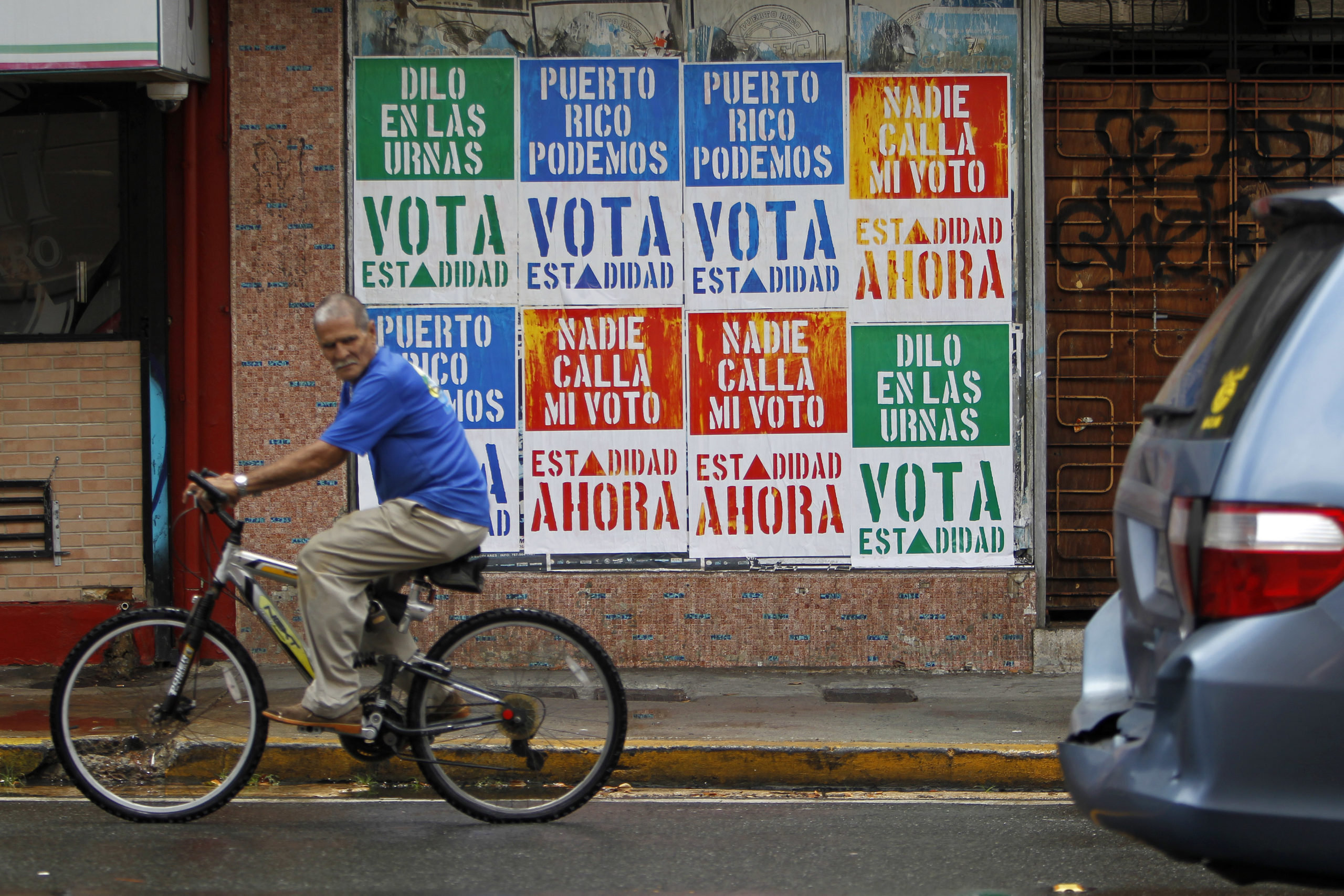 A rides his bicycle in front of a wall covered with campaign posters promoting Puerto Ricos statehood in San Juan, on June 9, 2017. A referendum on the political status of the US territory takes place on June 11, 2017. The US commonwealth of Puerto Rico votes on whether to become the 51st state. / AFP PHOTO / Ricardo ARDUENGO (Photo credit should read RICARDO ARDUENGO/AFP via Getty Images)