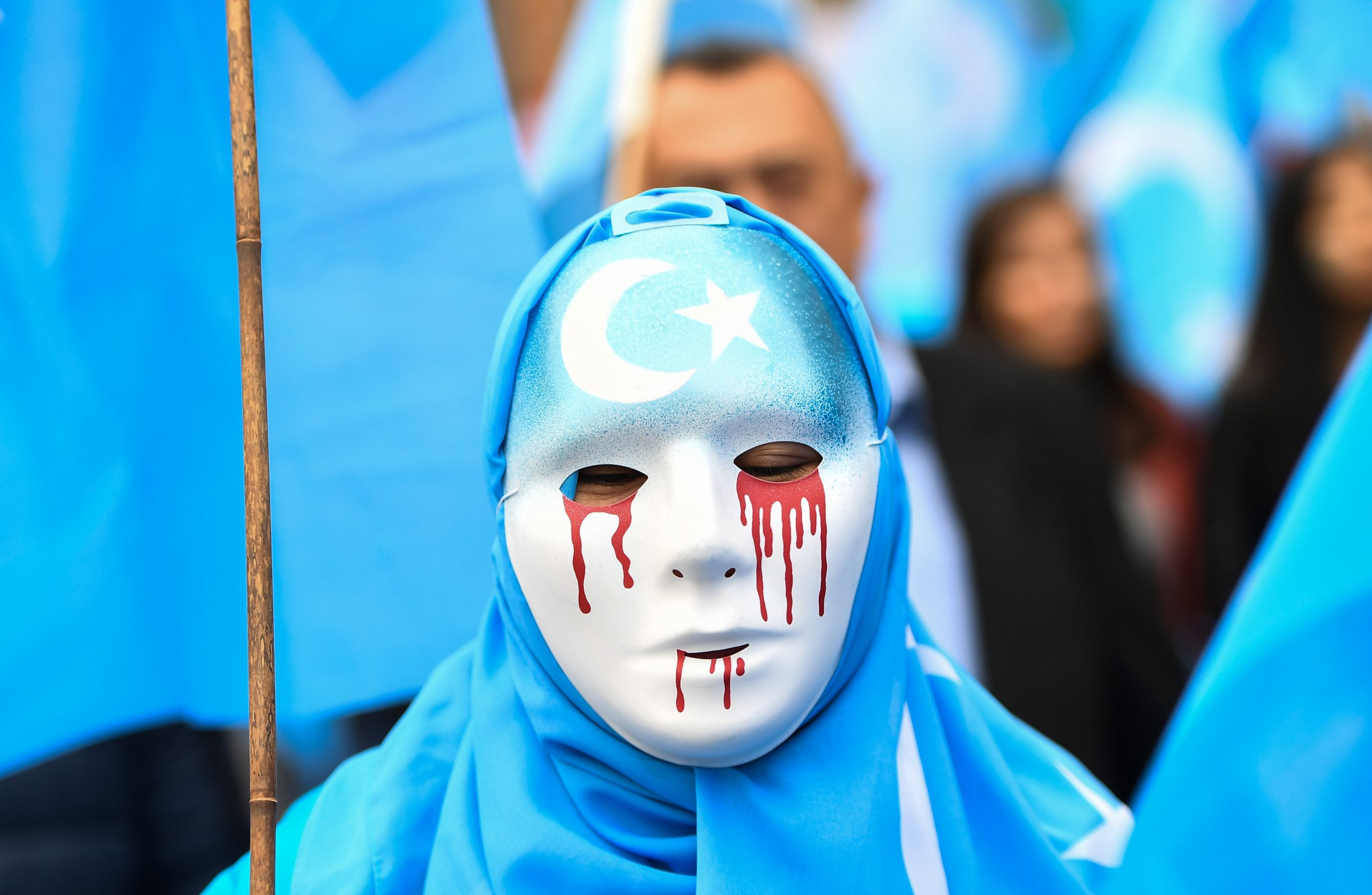"""TOPSHOT - A person wearing a white mask with tears of blood takes part in a protest march of ethnic Uighurs asking for the European Union to call upon China to respect human rights in the Chinese Xinjiang region and ask for the closure of """"re-education center"""" where Uighurs are detained, during a demonstration around the EU institutions in Brussels on April 27, 2018. (Photo by Emmanuel DUNAND / AFP) (Photo by EMMANUEL DUNAND/AFP via Getty Images)"""