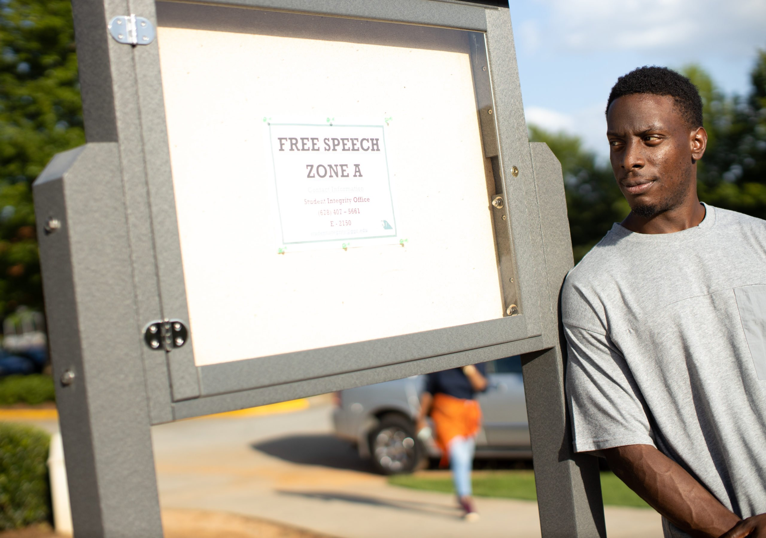 Chike Uzuegbunam stands next to a speech zone sign on the campus of Georgia Gwinnett College in Lawrenceville, Georgia. (Alliance Defending Freedom)