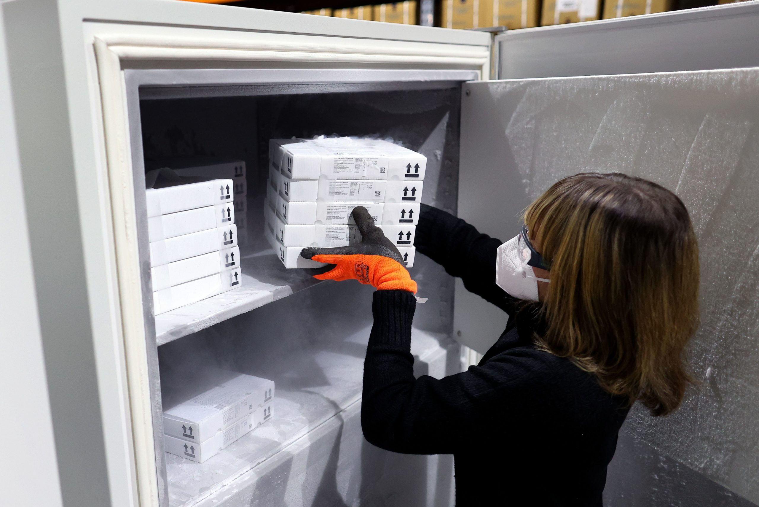 Employee Jessica Mueller puts the Pfizer-Biontech Covid-19 corona virus vaccine into an ultra-low freezer at the vaccine warehouse where the doses will be preserved before their distribution on January 08, 2021. (Photo by RONNY HARTMANN/AFP via Getty Images)