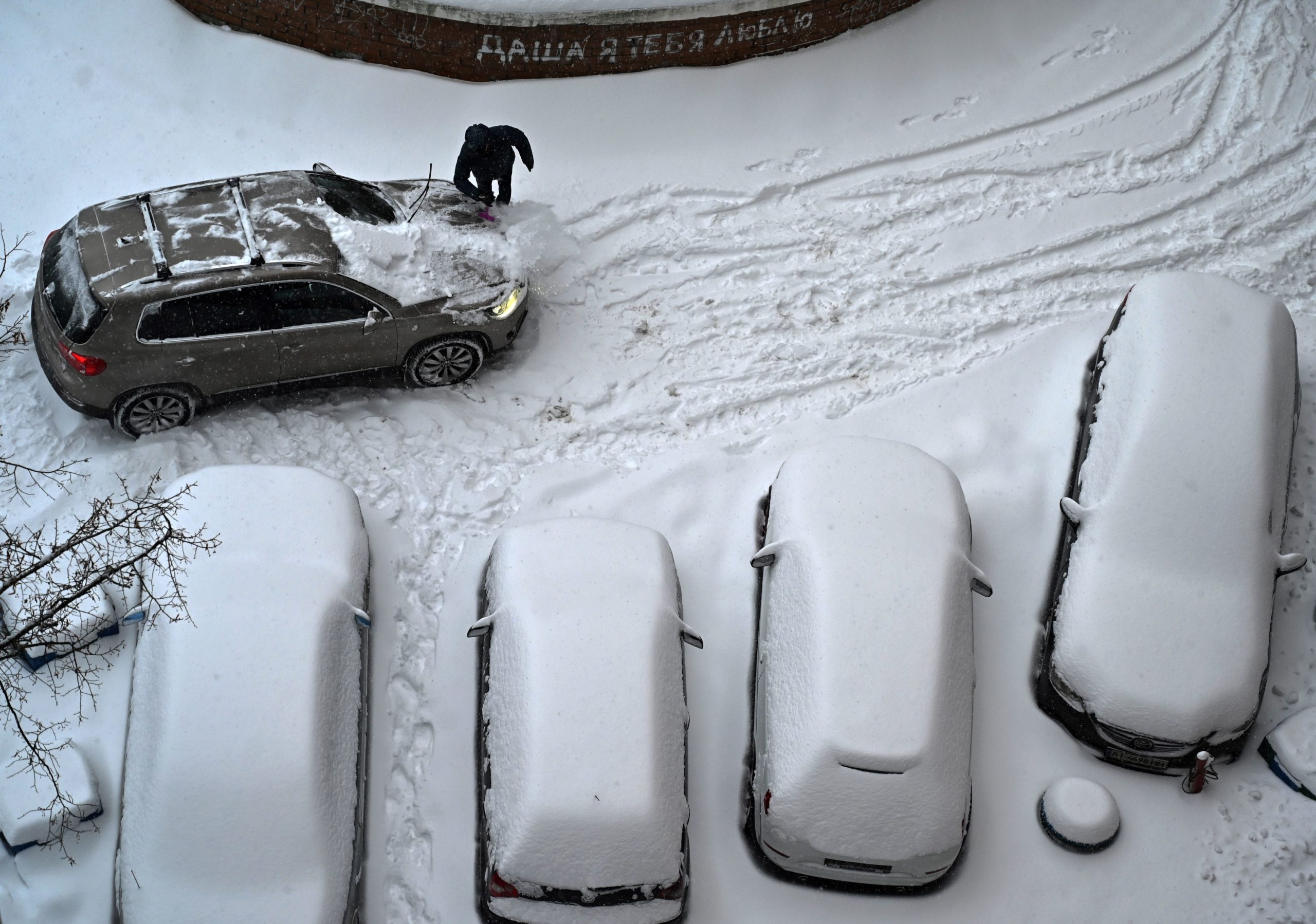 A man cleans his car from snow after a heavy night snowfall in the Ukrainian capital of Kiev on February 9, 2021. (Photo by Sergei SUPINSKY / AFP) (Photo by SERGEI SUPINSKY/AFP via Getty Images)