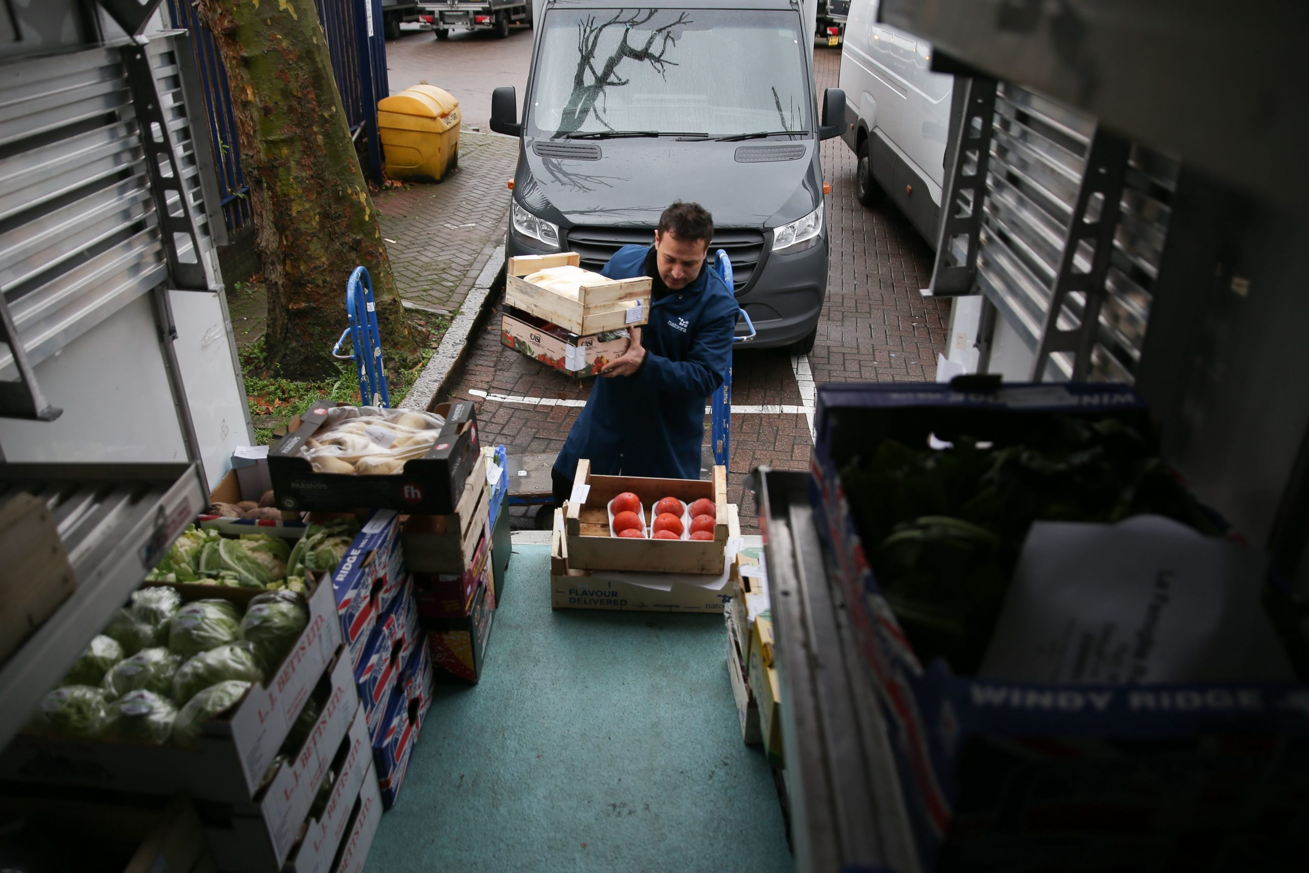 Workers load and unload boxes of fresh fruit and vegetables from trucks at the warehouse of Natoora, a fruit and vegetable distribution company, in south London on December 5, 2018. - Fruit and vegetable entrepreneur Franco Fubini knows all about the importance of goods arriving on time, as Brexit threatens to delay delivery of produce into and out of Britain. In an effort to prepare for a so-called hard Brexit following Britain's formal departure from the European Union on March 29, British companies are increasingly stating that they are preparing to stockpile items. While for some this is fairly straightforward, in the case of Fubini's company Natoora -- predominantly a wholesaler but also a shop retailer and food producer -- stockpiling fresh fruits and vegetables is not viable. (Photo by Daniel LEAL-OLIVAS / AFP) (Photo credit should read DANIEL LEAL-OLIVAS/AFP via Getty Images)