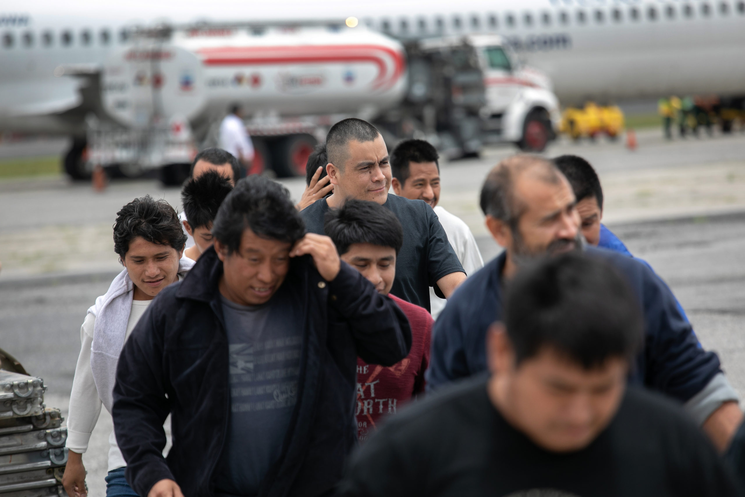 GUATEMALA CITY, GUATEMALA - MAY 30: Guatemalan men walk from a deportation flight, chartered by the U.S. Government, after being sent back from the United States on May 30, 2019 in Guatemala City, Guatemala. U.S. Immigration and Customs Enforcement (ICE) deports some 2,000 people per week to Guatemala from various U.S. cities. (Photo by John Moore/Getty Images)