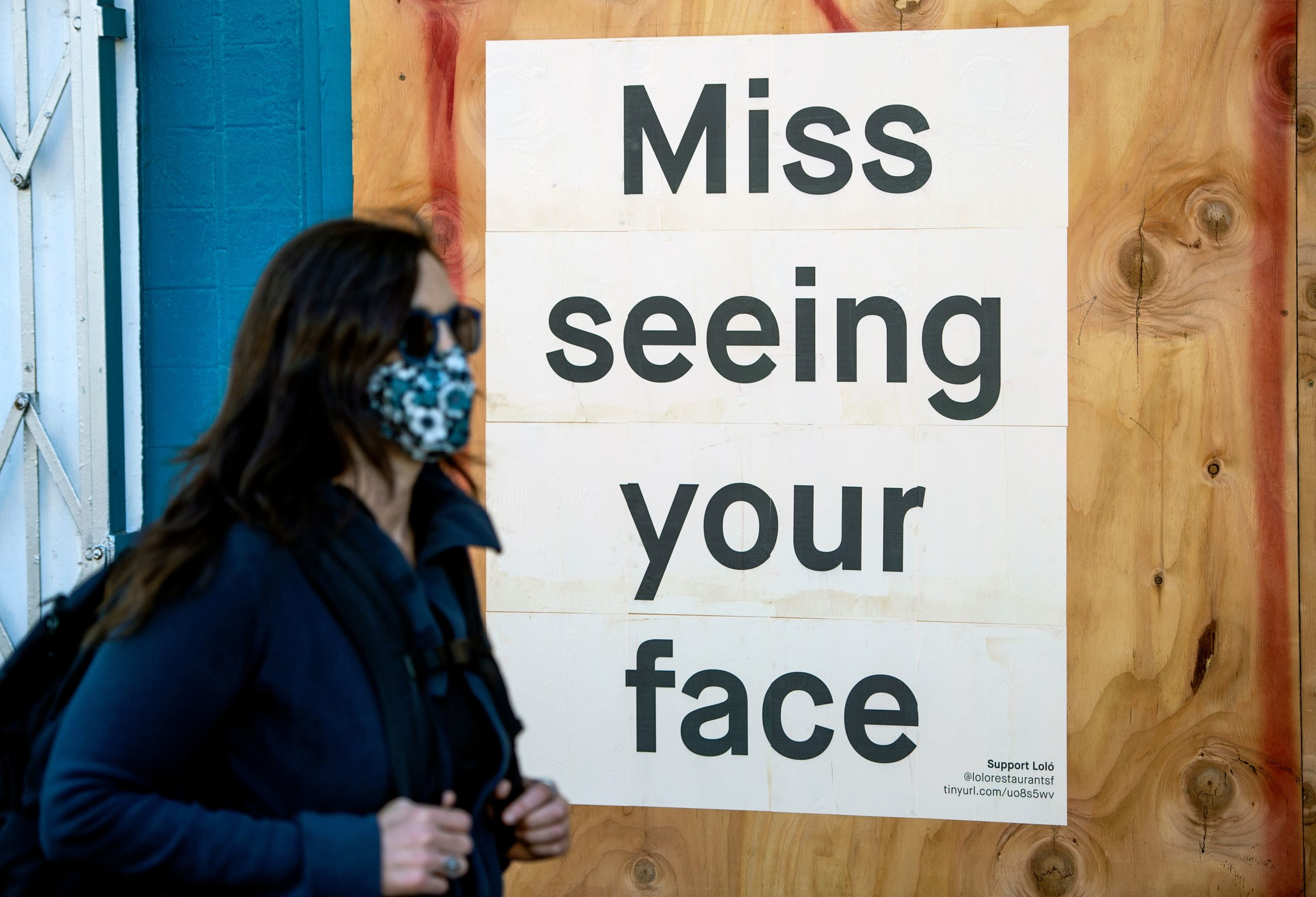 A woman in a face mask walks by a sign posted on a boarded up restaurant in San Francisco, California. (Josh Edelson/AFP via Getty Images)
