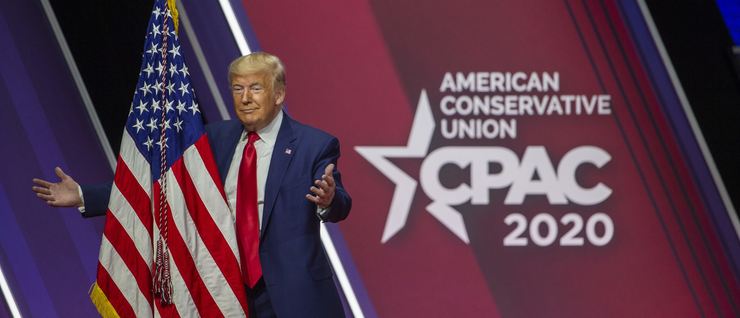 President Donald Trump hugs the flag of the United States of America at the annual Conservative Political Action Conference (CPAC). (Photo by Tasos Katopodis/Getty Images)