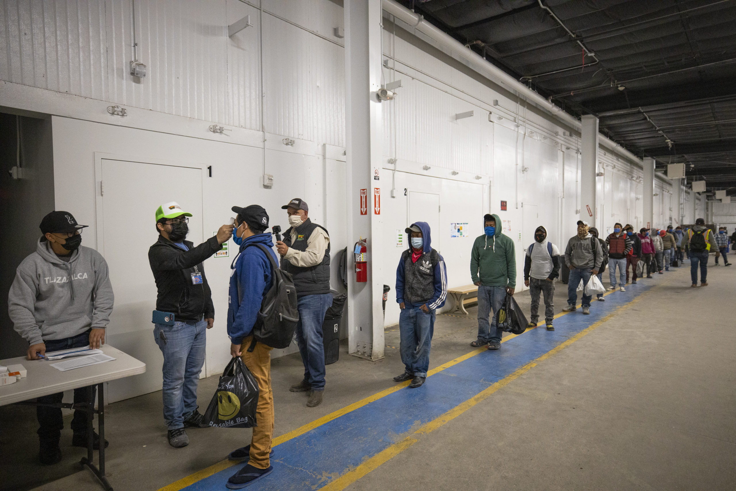 Migrant farm laborers have their temperature checked and are asked questions about their health before boarding the bus to their shift in King City, California last year. (Brent Stirton/Getty Images)