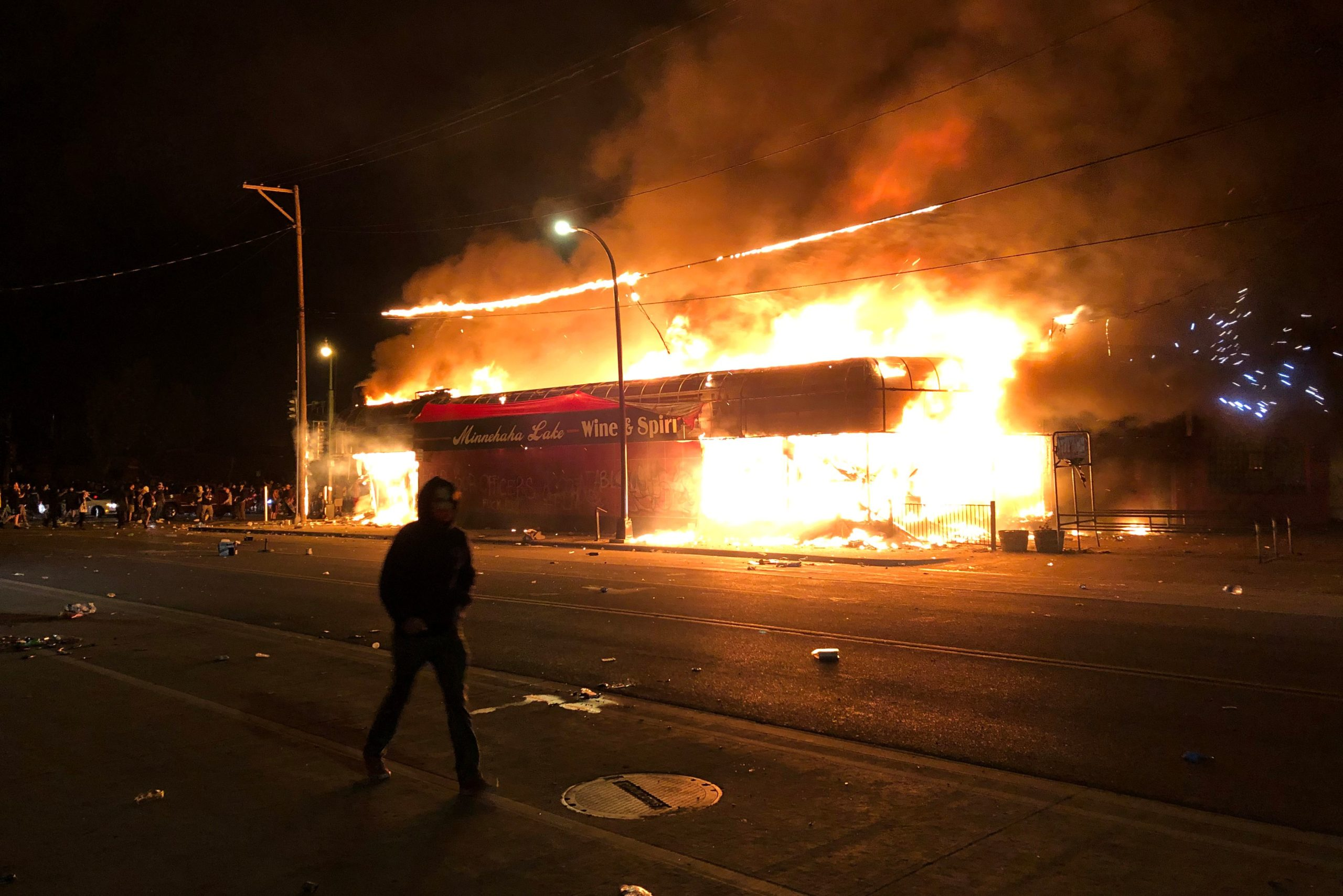 Flames rise from a liquor store near the Third Police Precinct on May 28, 2020 in Minneapolis, Minnesota, during a protest over the death of George Floyd, an unarmed black man, who died after a police officer kneeled on his neck for several minutes. - A police precinct in Minnesota went up in flames late on May 28 in a third day of demonstrations as the so-called Twin Cities of Minneapolis and St. Paul seethed over the shocking police killing of a handcuffed black man. The precinct, which police had abandoned, burned after a group of protesters pushed through barriers around the building, breaking windows and chanting slogans. A much larger crowd demonstrated as the building went up in flames. (Photo by Kerem Yucel / AFP) (Photo by KEREM YUCEL/AFP via Getty Images)