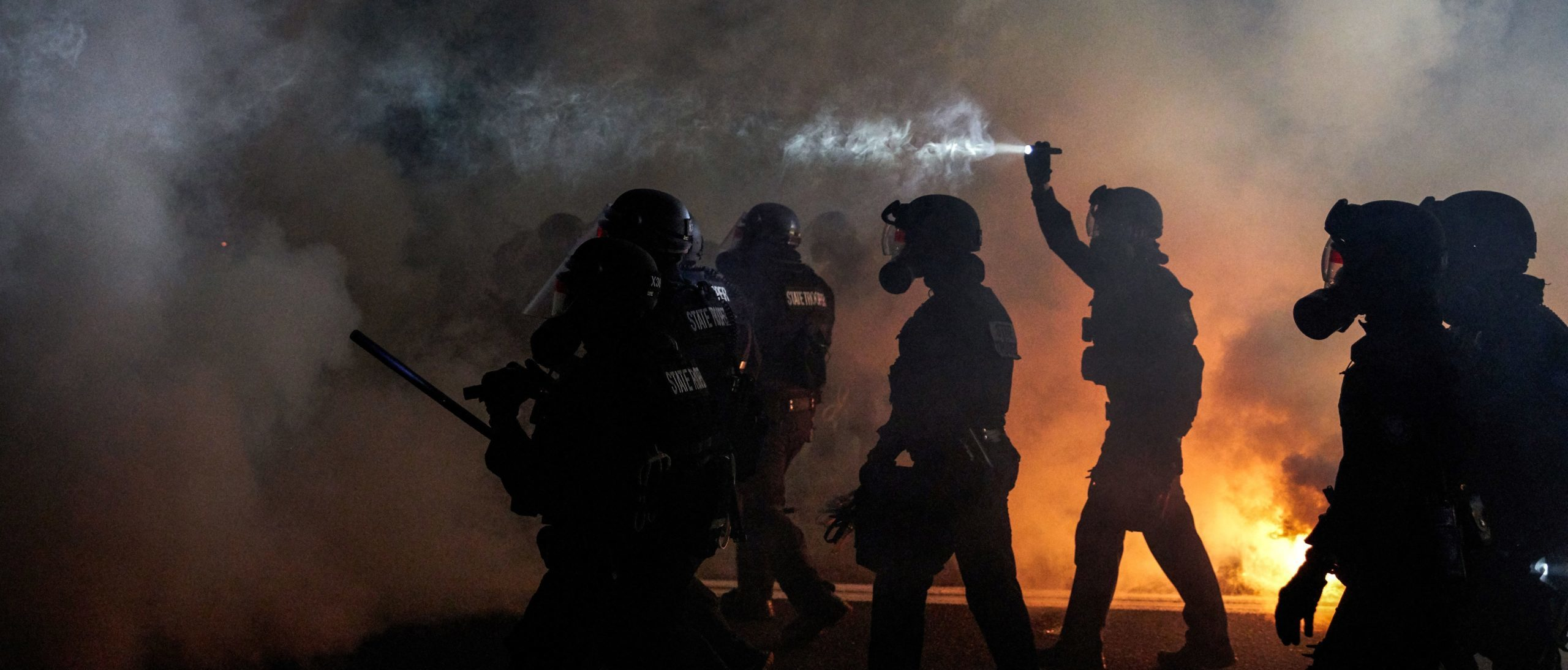 Oregon Police wearing anti-riot gear march towards protesters through tear gas smoke during the 100th day and night of protests against racism and police brutality in Portland, Oregon, on September 5, 2020. (Photo by ALLISON DINNER/AFP via Getty Images)