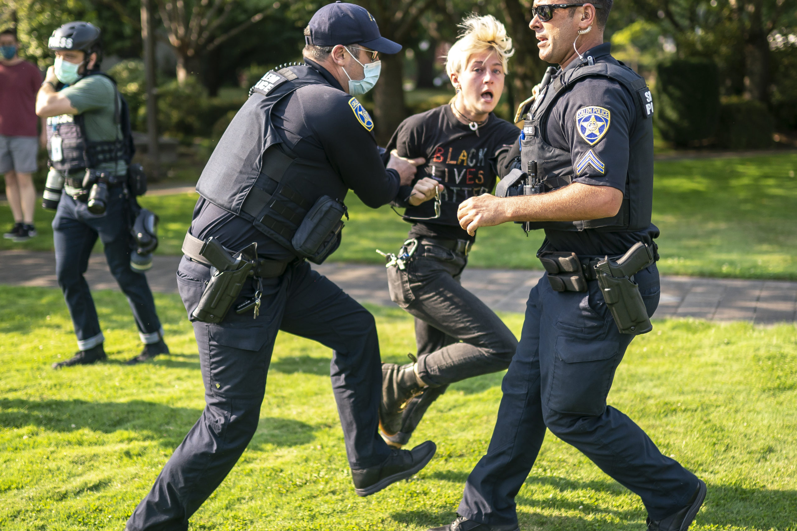 SALEM OR - SEPTEMBER 7: Salem police escort a counter protester away from the scene after a clash with a far-right protester on September 7, 2020 in Portland, Oregon. A Pro-Trump caravan drove into the Oregon state capitol Monday afternoon where far-right protesters clashed with counter-protesters. (Photo by Nathan Howard/Getty Images)