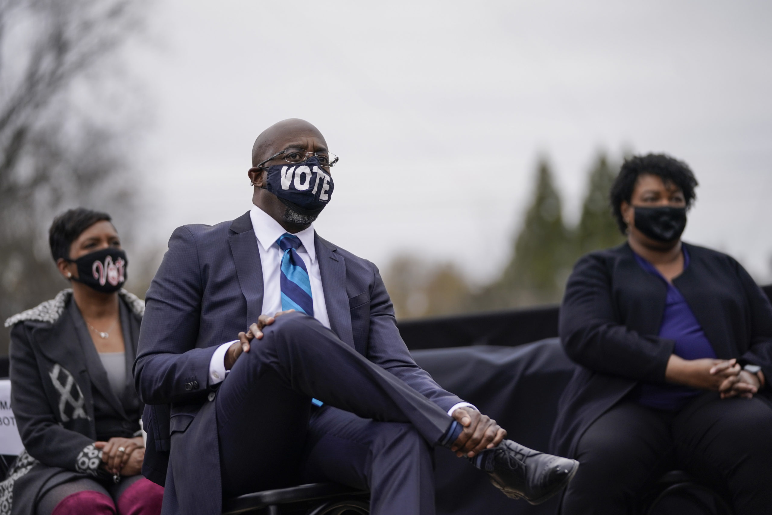 ATLANTA, GA - DECEMBER 15: (L-R) Atlanta Mayor Keisha Lance Bottoms, U.S. Democratic Senate candidate Raphael Warnock and Stacey Abrams listen as U.S. President-elect Joe Biden speaks during a campaign rally at Pullman Yard on December 15, 2020 in Atlanta, Georgia. Biden's stop in Georgia comes less than a month before the January 5 runoff election for Ossoff and Warnock as they try to unseat Republican incumbents Sen. David Perdue and Sen. Kelly Loeffler. (Photo by Drew Angerer/Getty Images)