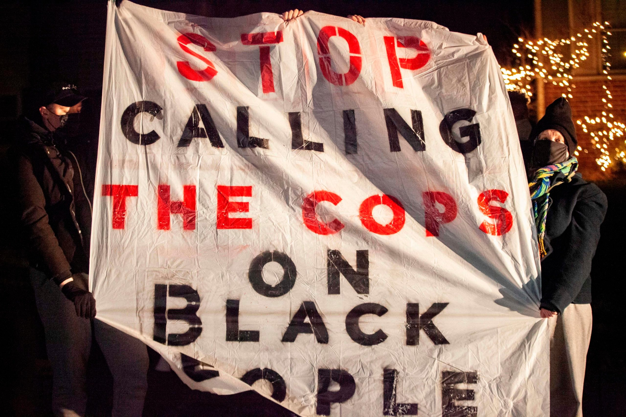 """People hold signs as they participate in a call to action """"White People Stop Calling the Cops on Black People"""" protest. (Photo by STEPHEN ZENNER / AFP) (Photo by STEPHEN ZENNER/AFP via Getty Images)"""