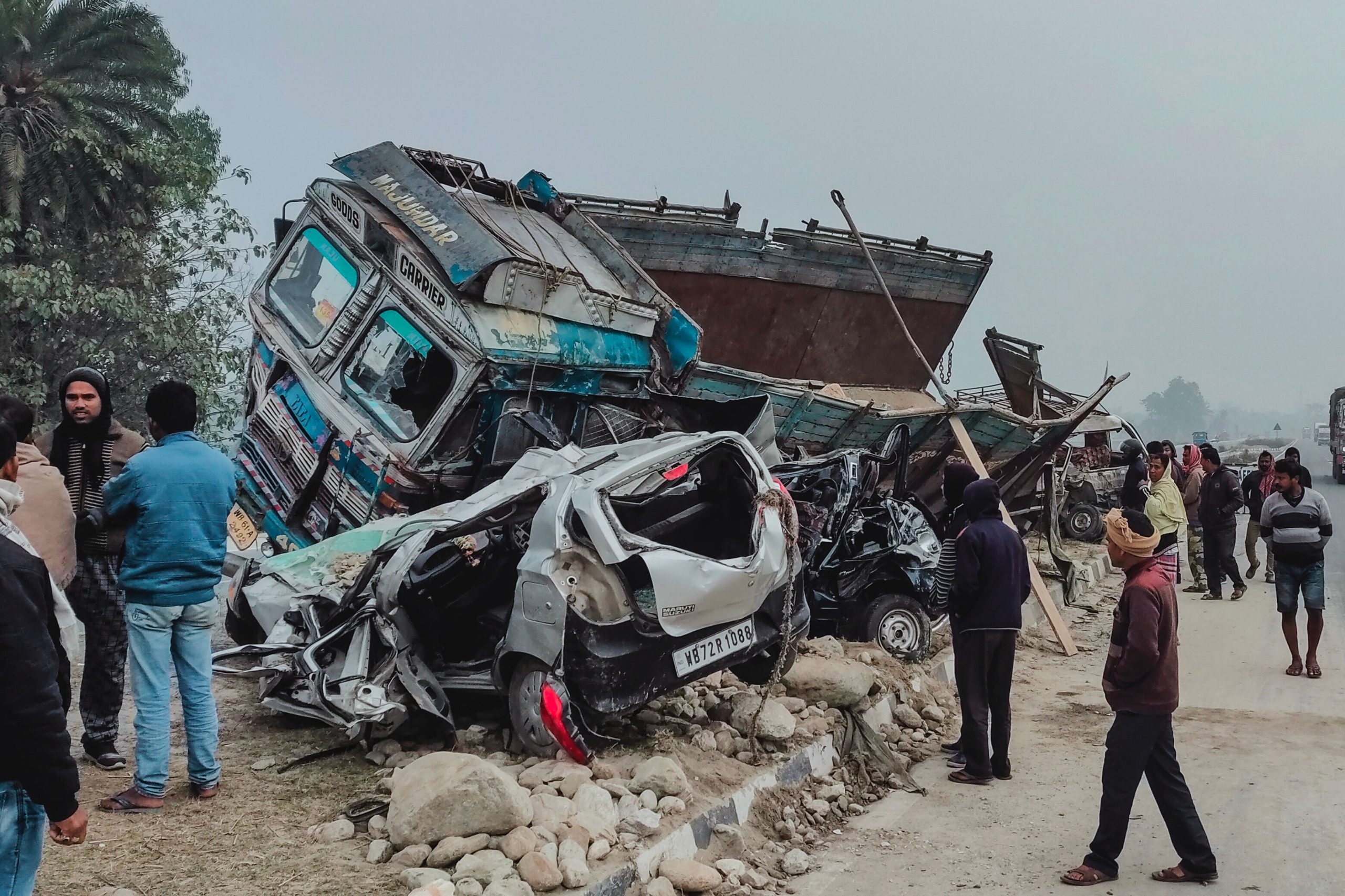 Onlookers stand near the wreckage of cars and a truck following a road accident in Dhupguri, Jalpaiguri district, on January 20, 2021. (Photo by - / AFP) (Photo by -/AFP via Getty Images)