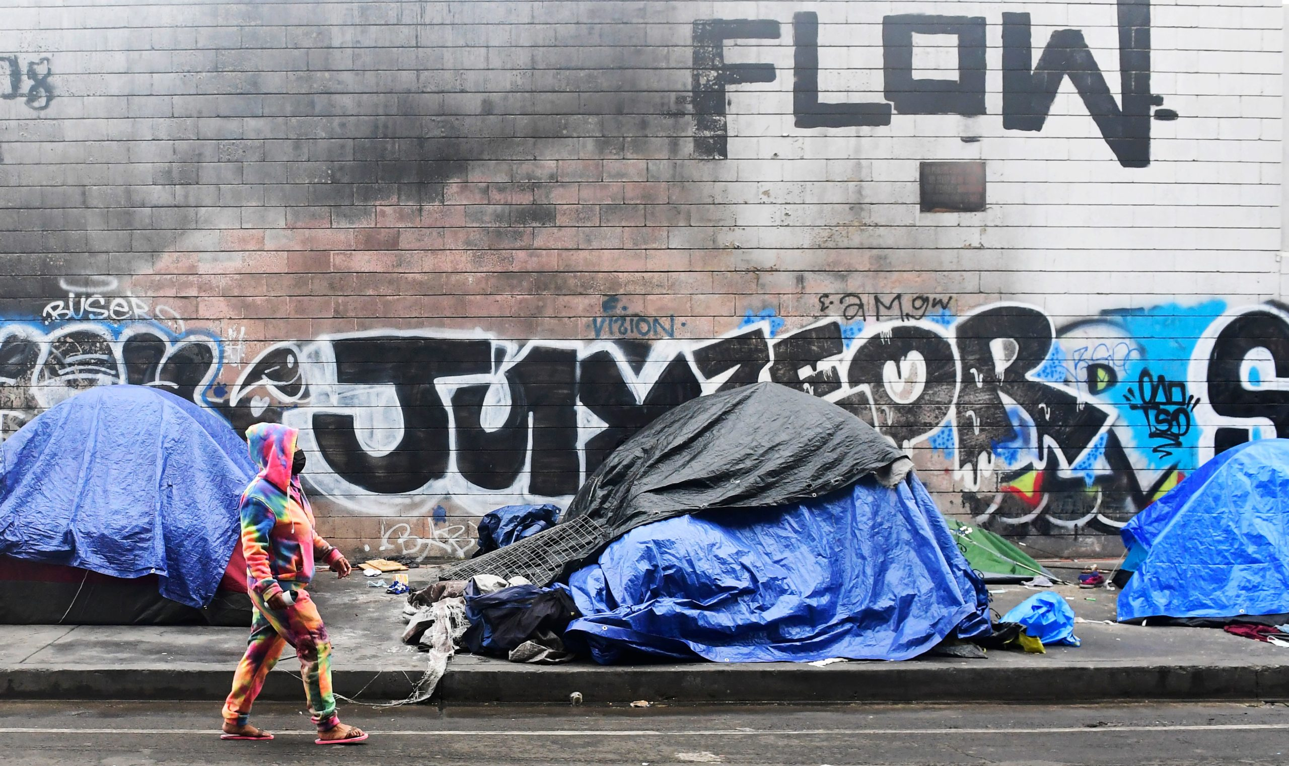 A woman walks past tents for the homeless lining a street in Los Angeles, California on Monday. The U.S.recorded its sharpest rise in poverty since the 1960s when the poverty rate spiked to 11.8% in December. (Frederic J. Brown/AFP via Getty Images)