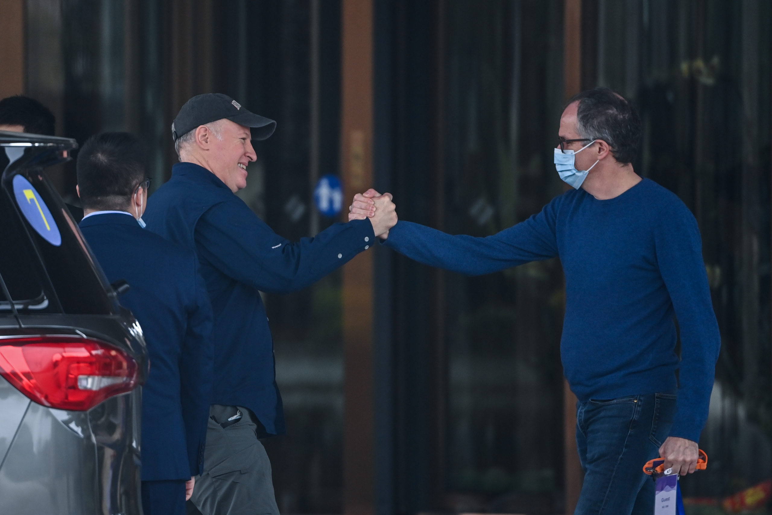 WHO team members Peter Daszak (L) and Peter Ben Embarek (R) shake hands as Daszak leaves the hotel after the World Health Organization (WHO) team wrapped up its investigation into the origins of the COVID-19 coronavirus in Wuhan in China's central Hubei province on February 10, 2021. (HECTOR RETAMAL/AFP via Getty Images)