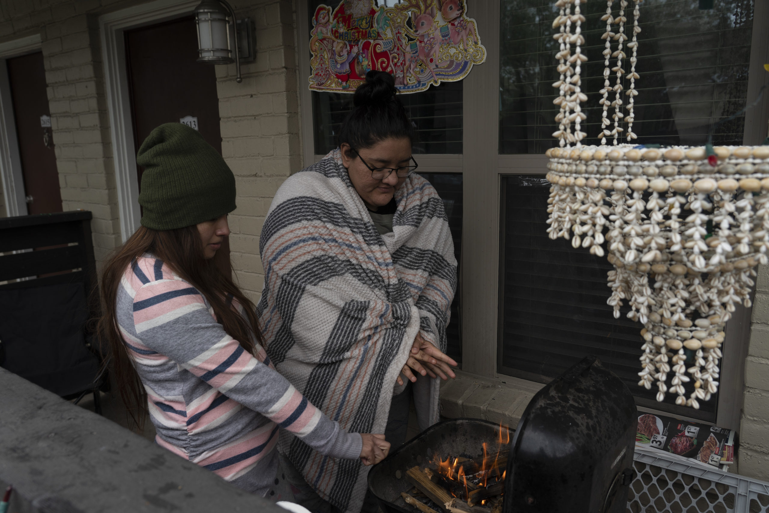 HOUSTON, TX - FEBRUARY 16: Karla Perez and Esperanza Gonzalez warm up by a barbecue grill during power outage caused by the winter storm on February 16, 2021 in Houston, Texas. Winter storm Uri has brought historic cold weather, power outages and traffic accidents to Texas as storms have swept across 26 states with a mix of freezing temperatures and precipitation. (Photo by Go Nakamura/Getty Images)