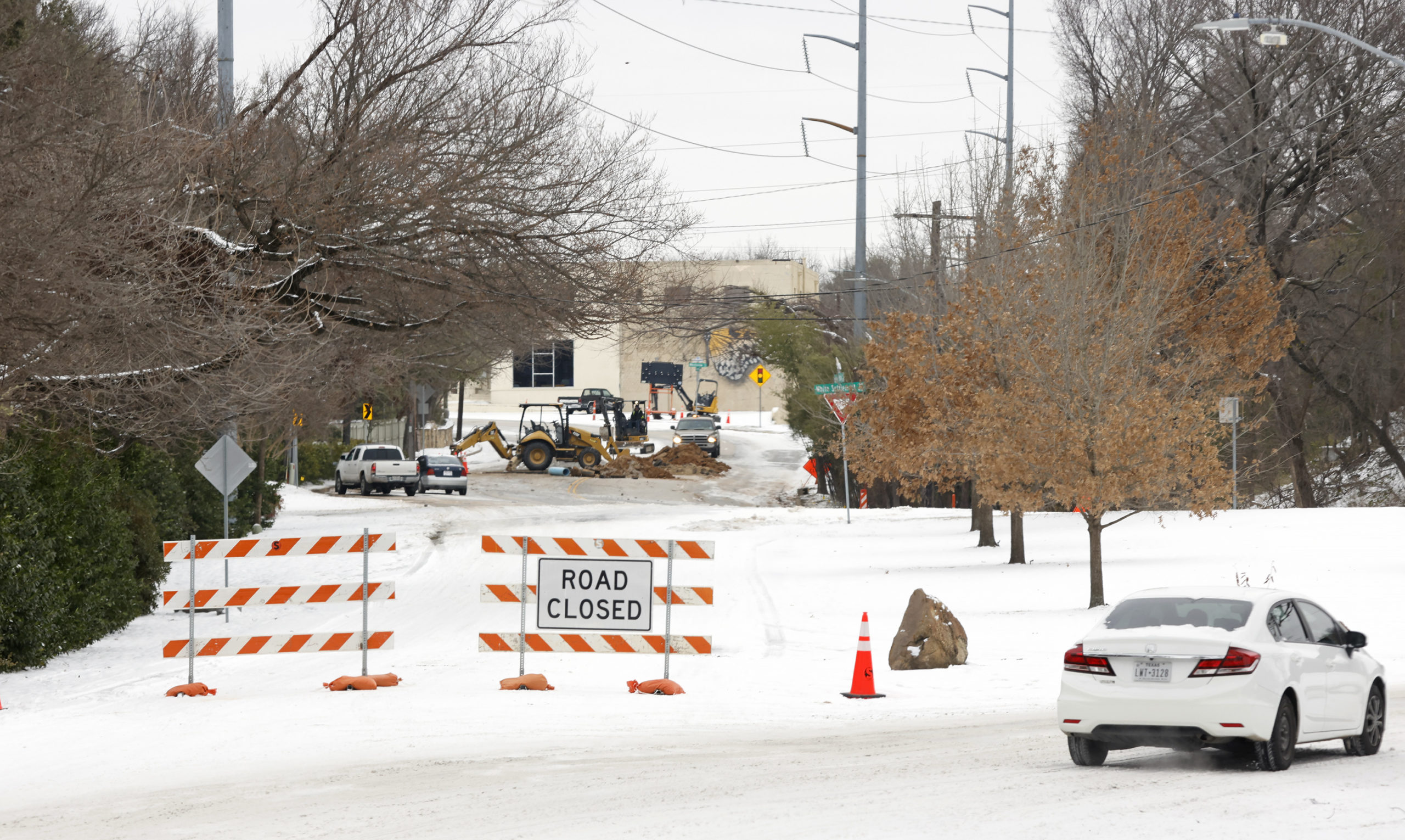 FORT WORTH, TX - FEBRUARY 18: Drivers detour around a water pipe repair crew after a snow storm on February 18, 2021 in Fort Worth, Texas. Winter storm Uri has brought historic cold weather and power outages to Texas. Residents have gone days without electricity and fresh water after a catastrophic failure of the power grid in the state. (Photo by Ron Jenkins/Getty Images)