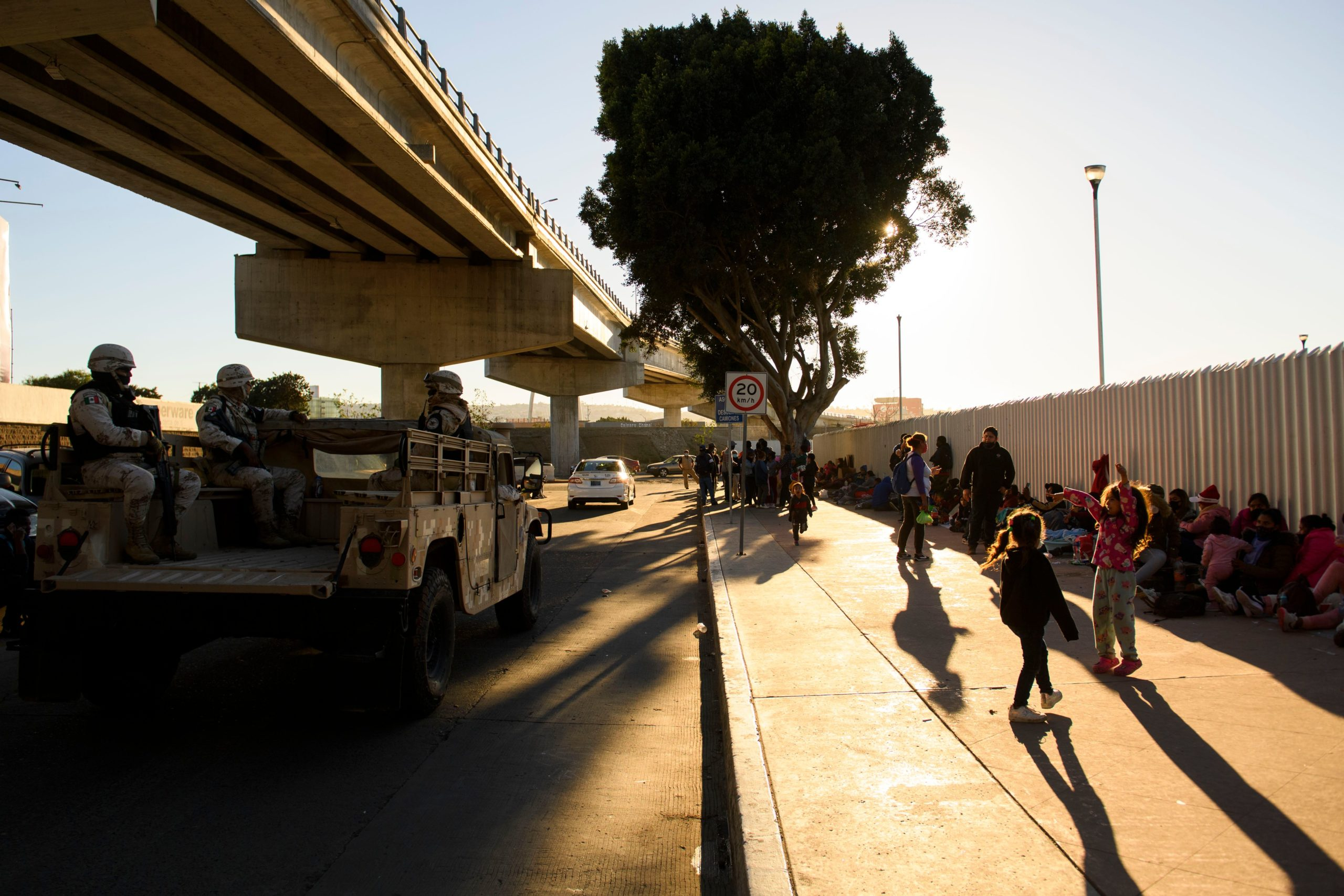 TOPSHOT - A Mexican National Guard vehicle drives past children playing as families of asylum seekers wait outside the El Chaparral border crossing port as they wait to cross into the United States in Tijuana, Baja California state, Mexico on February 19, 2021. - The Biden administration plans to slowly allow 25,000 people with active cases seeking asylum into the US previously enrolled in the Migrant Protection Protocols program, known as