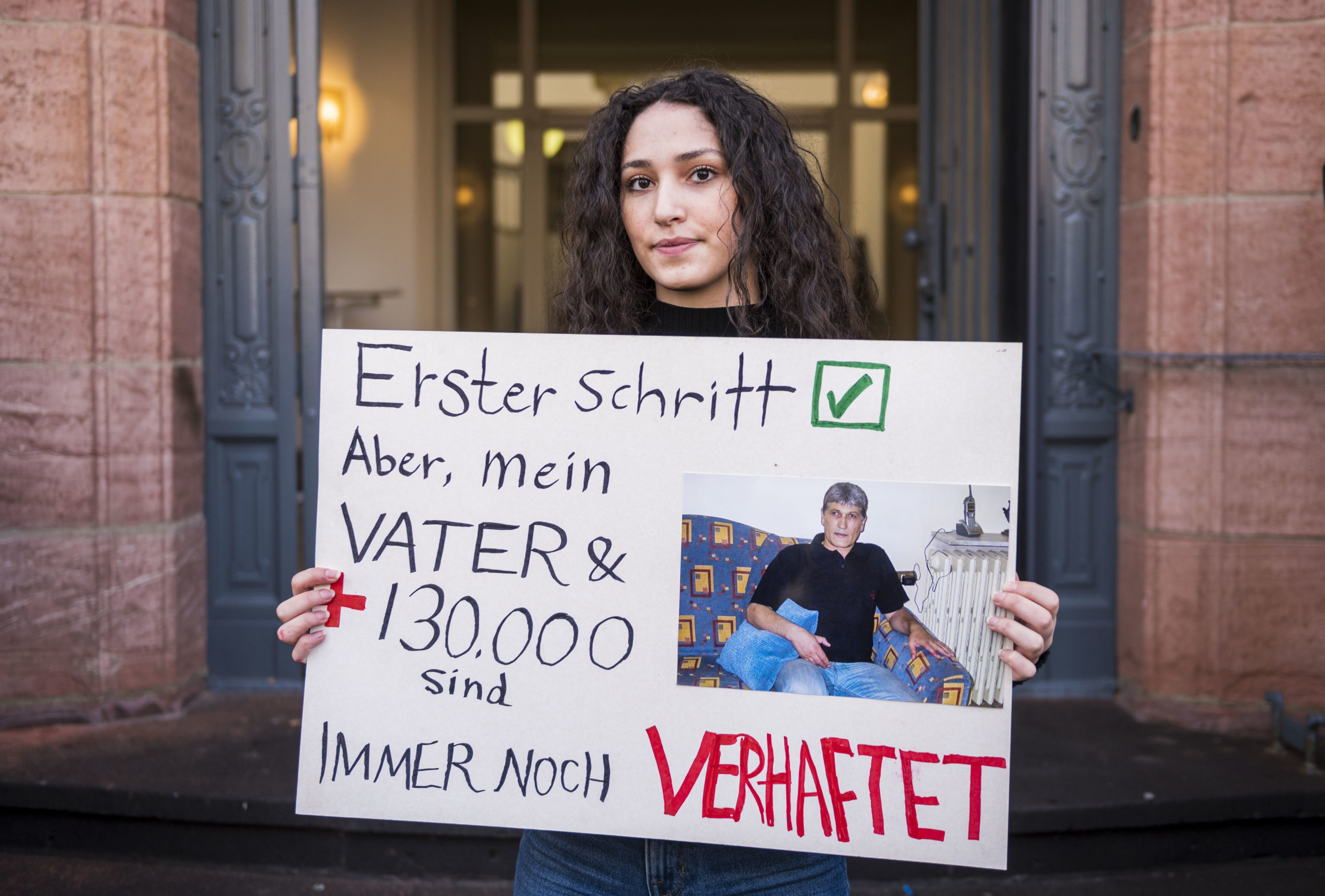 Sedra Alshehabi stands with a placard with the picture of her father Ali and a text reading 'First step but my father and 130000 are still in jail' after the verdict in the trail of Syrian defendant Eyad al-Gharib, accused of crimes against humanity in the first trial of its kind to emerge from the Syrian conflict on February 24, 2021 in Koblenz, western Germany. - Eyad al-Gharib, 44, former Syrian intelligence service agent was sentenced to four and a half years in jail for complicity in crimes against humanity in the first court case over state-sponsored torture by the Syrian government. (Photo by Thomas Lohnes/AFP via Getty Images)