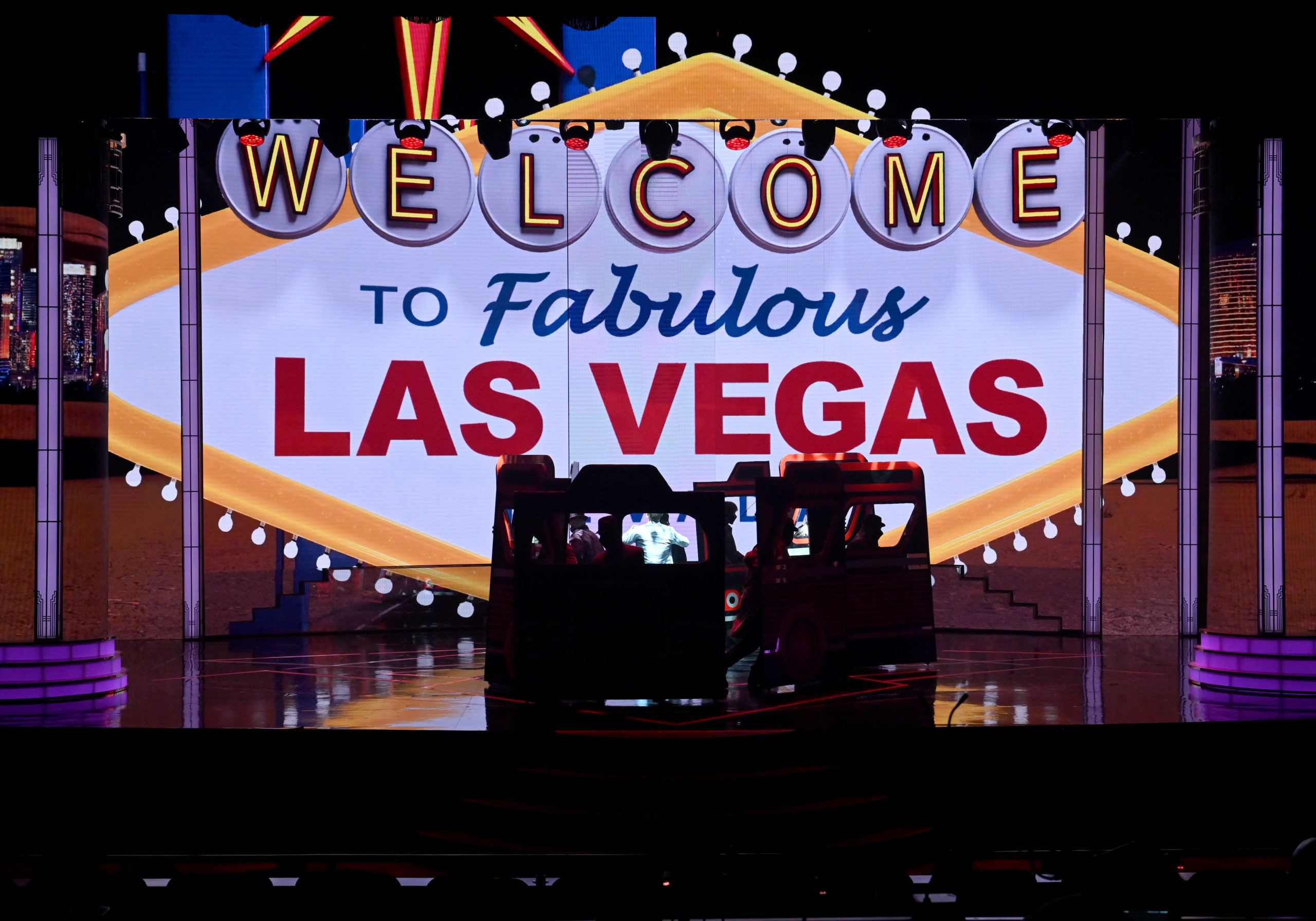 "LAS VEGAS, NEVADA - NOVEMBER 28: A prop bus is silhouetted onstage in front of a projection of the Welcome to Fabulous Las Vegas sign during the ""EXTRAVAGANZA - The Vegas Spectacular"" show at the Jubilee Theater at Bally's Las Vegas Hotel & Casino on November 28, 2020 in Las Vegas, Nevada. The production opened on March 14, 2020, for only one show before all entertainment on the Las Vegas Strip was shut down to fight the coronavirus (COVID-19) pandemic. The show reopened this week just as a three-week statewide pause went into effect due to surging COVID-19 numbers, forcing producers to adjust to new capacity restrictions limiting audience sizes to 50 people. (Photo by Ethan Miller/Getty Images)"