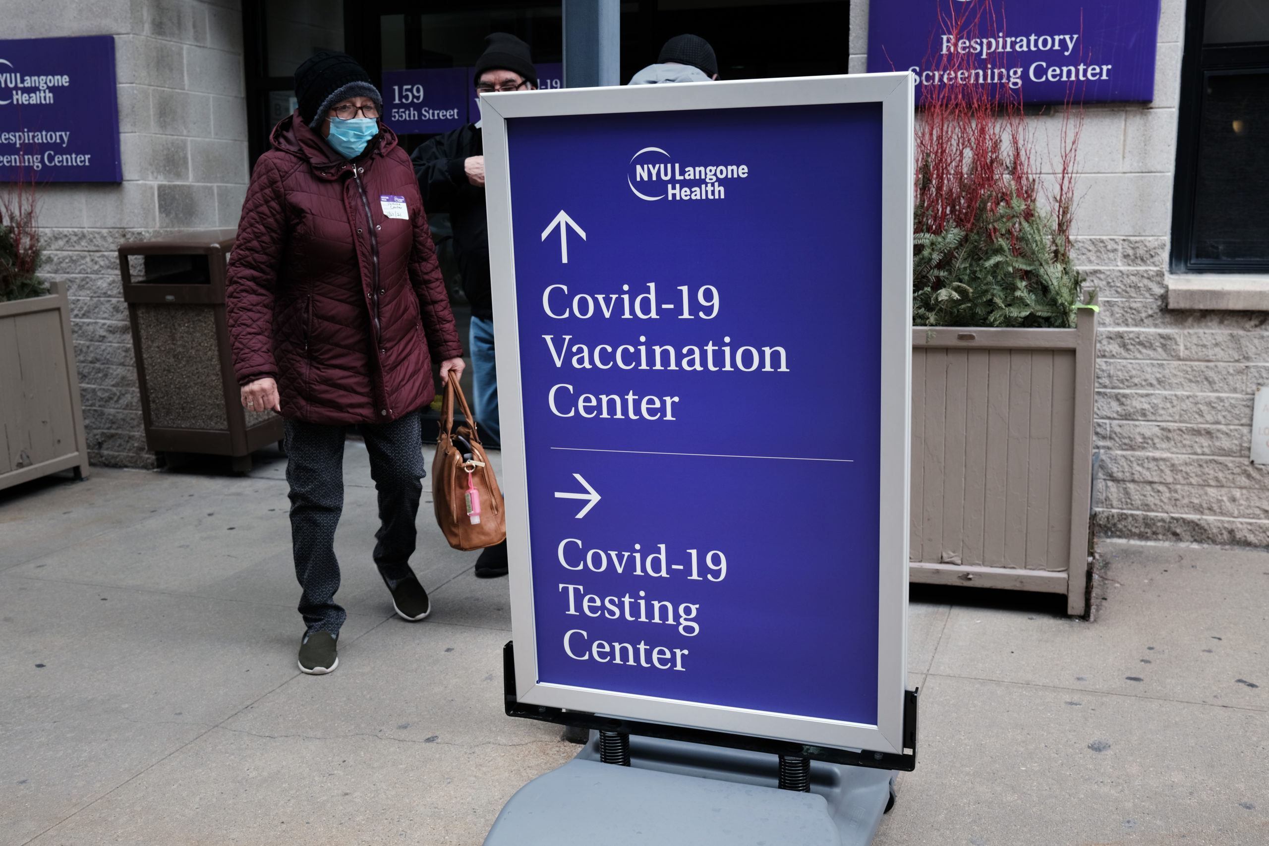 People walk by a sign for both a Covid-19 testing clinic and a Covid vaccination location on Jan. 27 in New York City. (Spencer Platt/Getty Images)