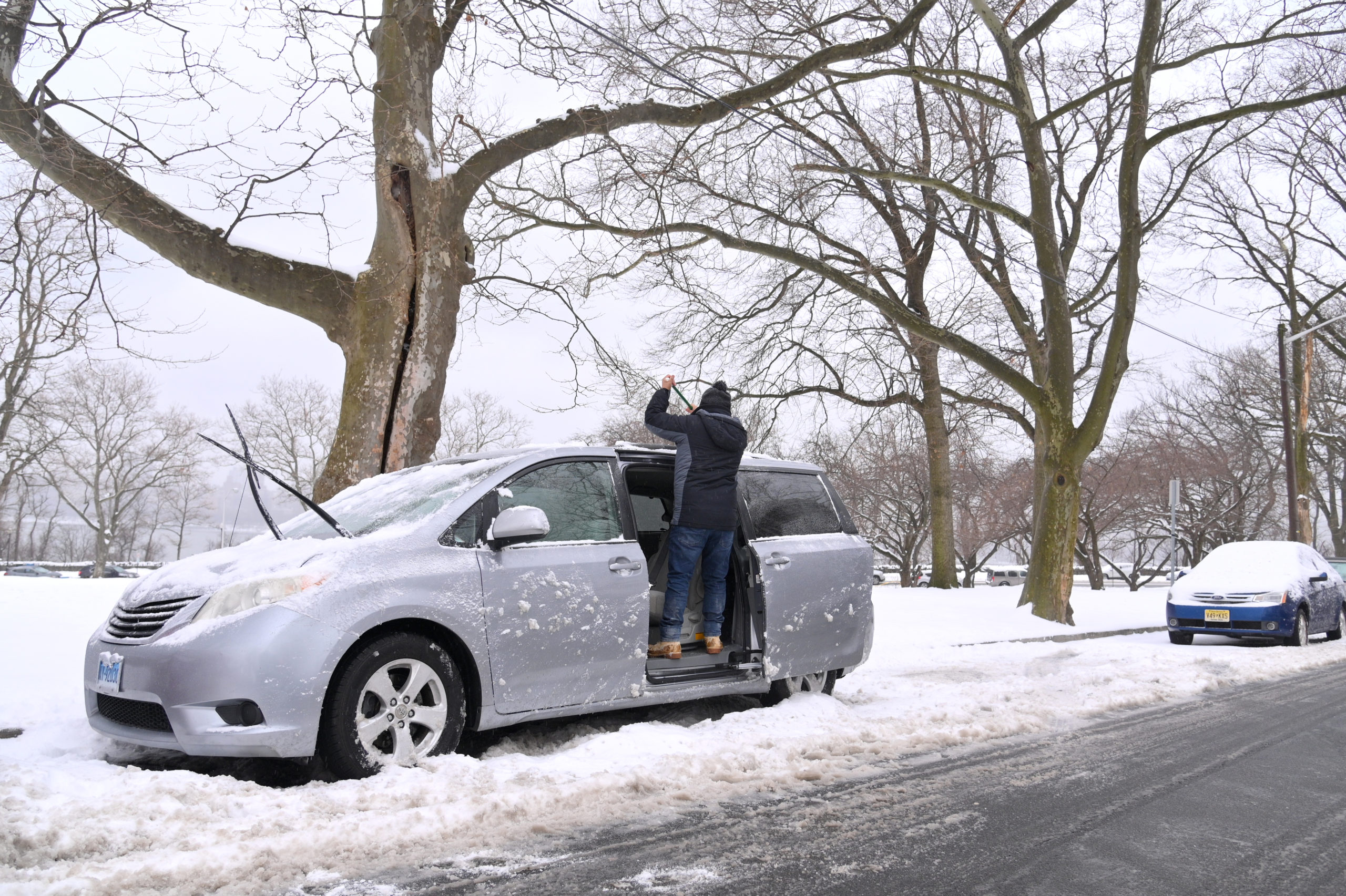 NORTH BERGEN, NEW JERSEY - FEBRUARY 18: A man brushes snow off of the roof of his car at James J. Braddock Park on February 18, 2021 in North Bergen, New Jersey. Snow accumulation has shut down more New Jersey vaccine sites and has been a strain on timely vaccine delivery. (Photo by Michael Loccisano/Getty Images)
