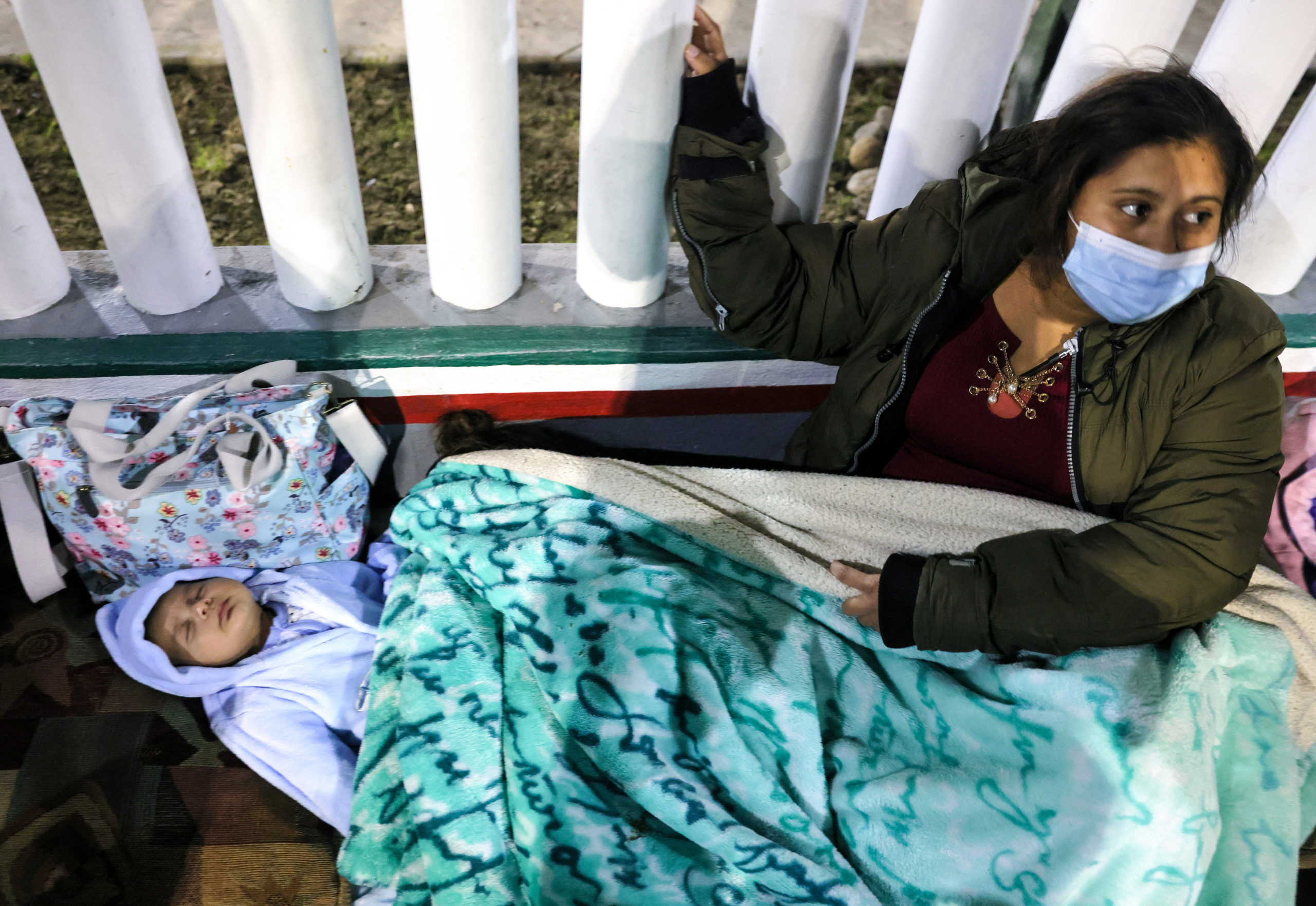 A Honduran mother sits with her one-month-old son and others who are seeking asylum in the United States outside the El Chaparral border crossing in the early morning hours on Feb. 19 in Tijuana, Mexico. (Mario Tama/Getty Images)