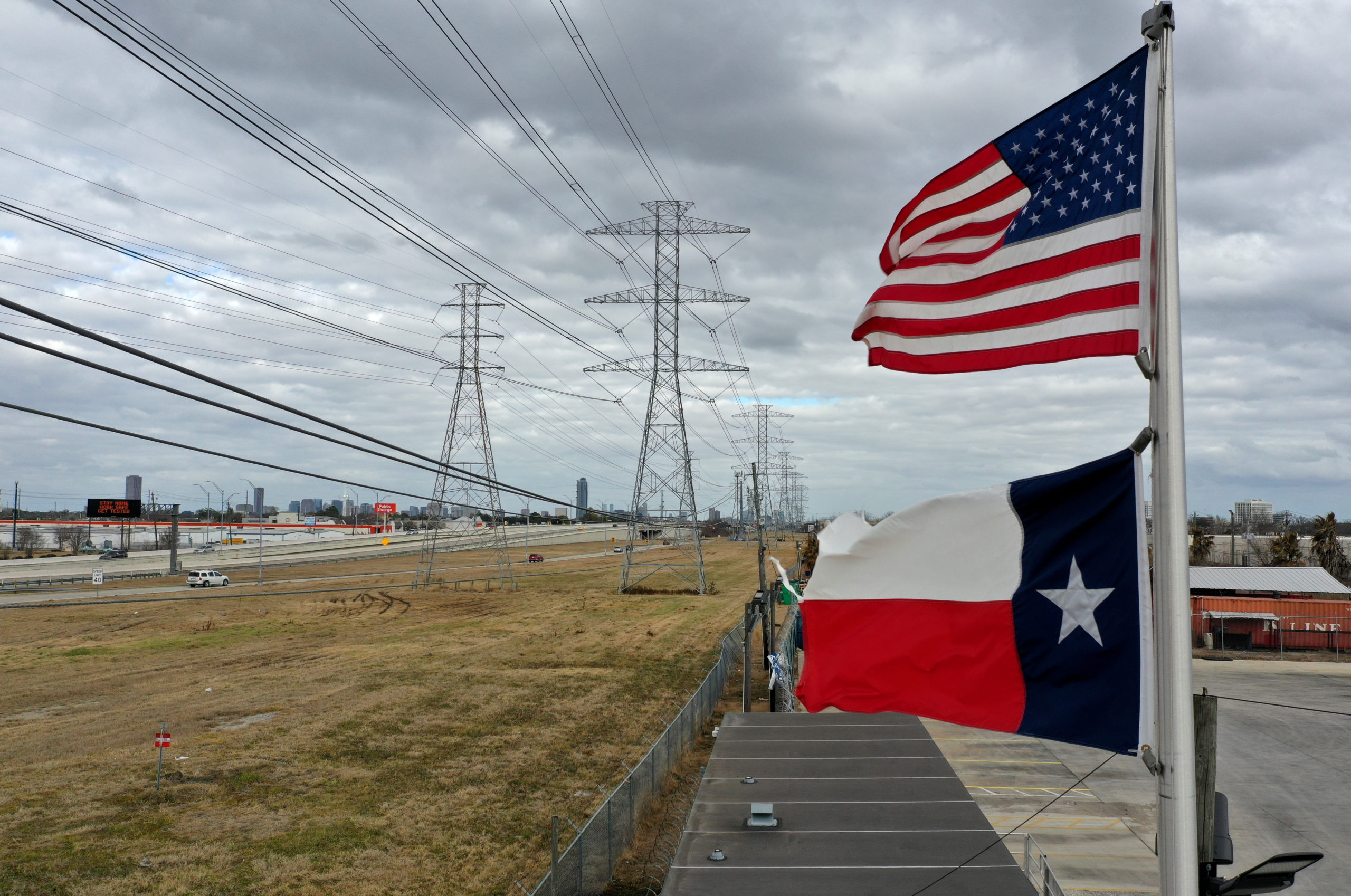 HOUSTON, TEXAS - FEBRUARY 21: The U.S. and Texas flags fly in front of high voltage transmission towers on February 21, 2021 in Houston, Texas. (Photo by Justin Sullivan/Getty Images)