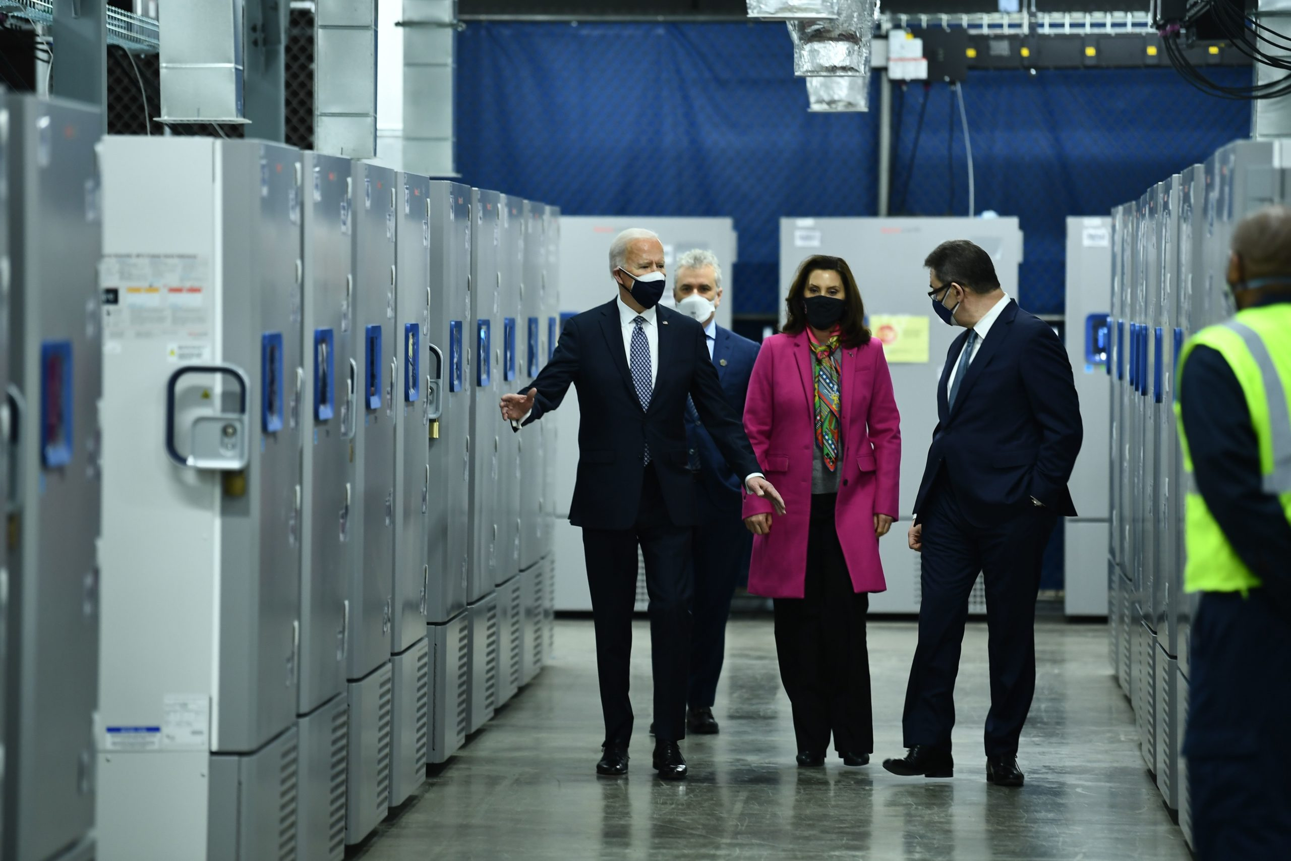 President Joe Biden, with Michigan Governor Gretchen Whitmer and Pfizer CEO Albert Bourla, tours Covid-19 vaccine freezers at a Pfizer manufacturing site on February 19, 2021, in Kalamazoo, Michigan. (BRENDAN SMIALOWSKI/AFP via Getty Images)