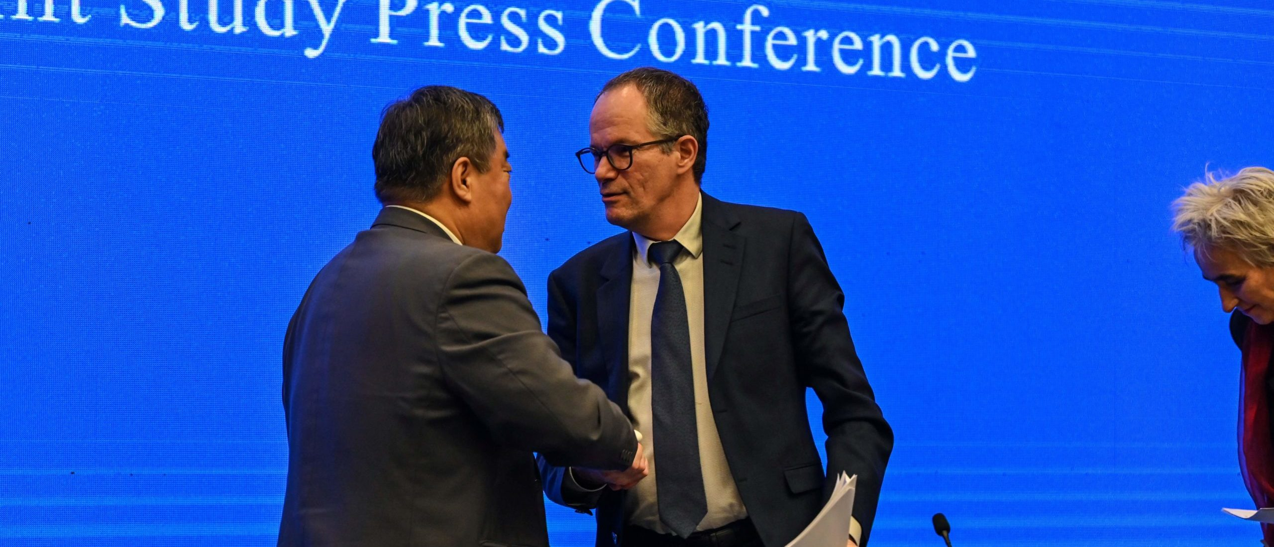 Peter Ben Embarek (R) shakes hands with Liang Wannian (L) after a press conference following a visit by the international team of experts from the World Health Organization (WHO) in the city of Wuhan, in China's Hubei province on February 9, 2021. (Photo by Hector RETAMAL / AFP) (Photo by HECTOR RETAMAL/AFP via Getty Images)
