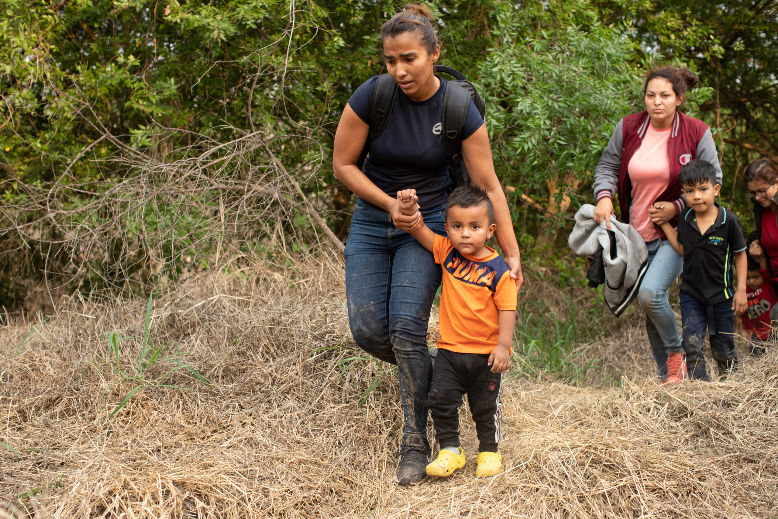 Illegal migrants approach law enforcement officials after they were smuggled into the U.S. to attempt to apply for asylum in Rincon Village near McAllen, Texas, on March 24, 2021. (Kaylee Greenlee – Daily Caller News Foundation)