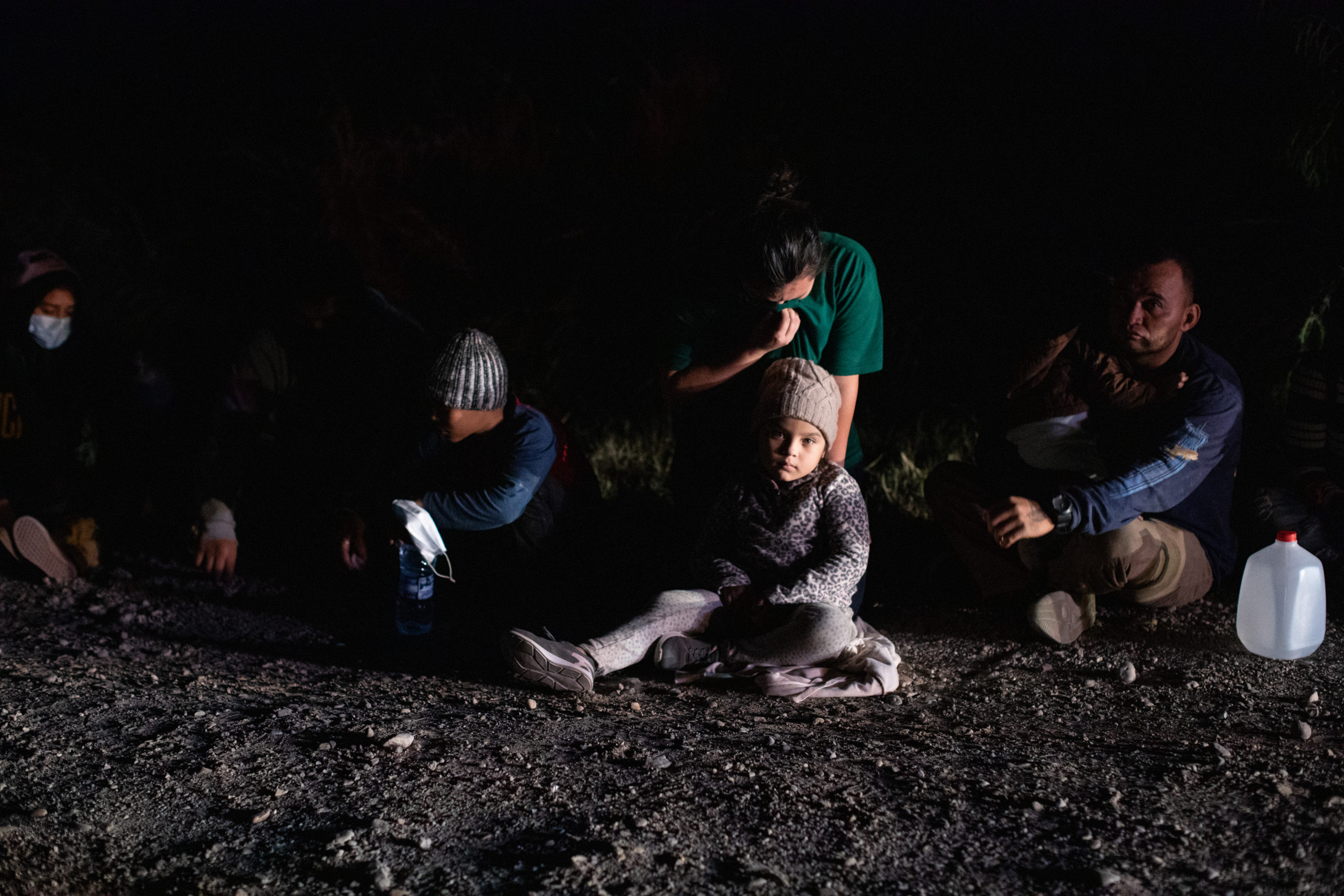 Illegal migrants sit in a line and wait to be processed by law enforcement officials who gathered biometrical data from them before transporting them to a processing facility in La Joya, Texas, on March 25, 2021. (Kaylee Greenlee. - Daily Caller News Foundation)