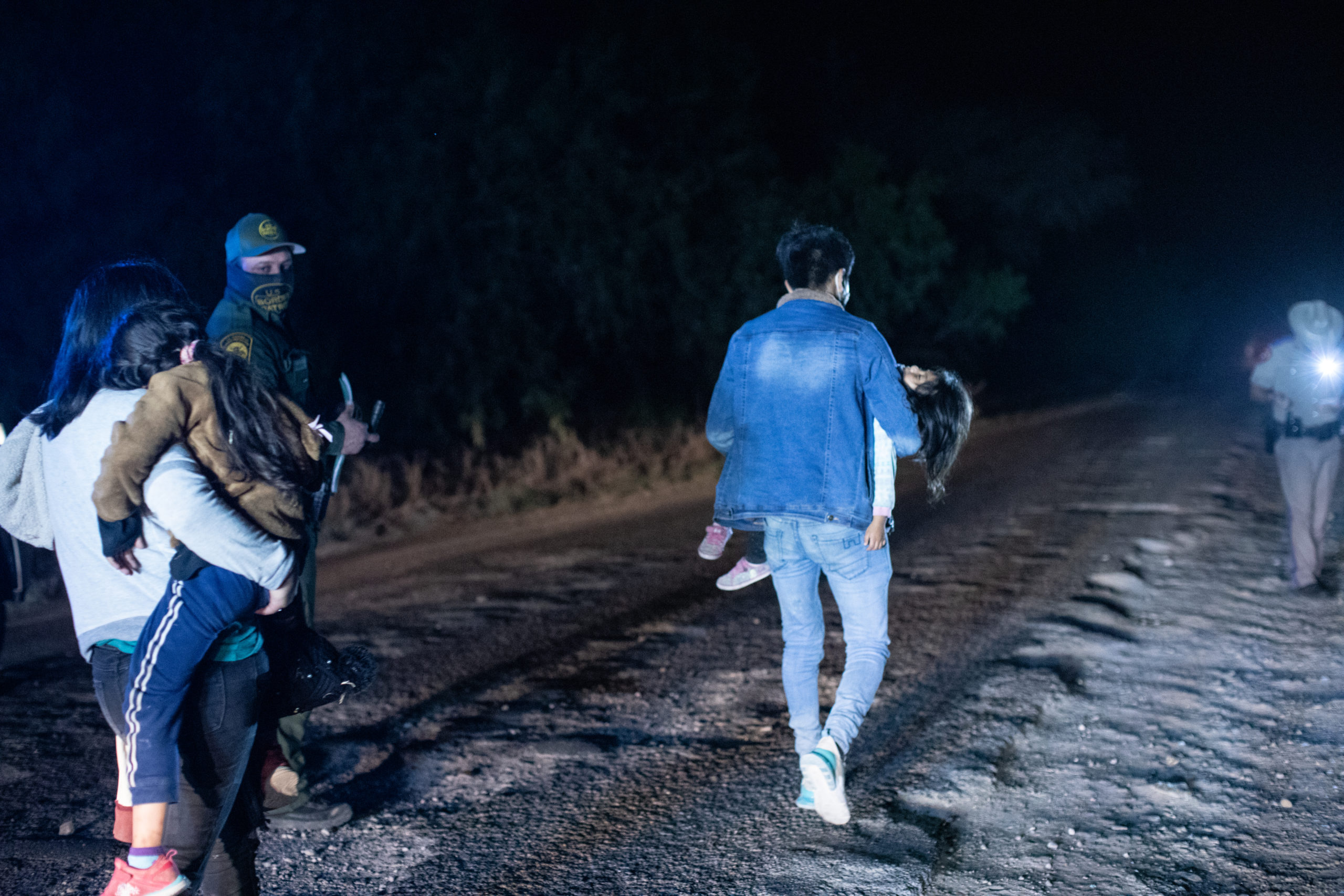 Illegal migrants walk towards law enforcement officials who gathered biometrical data from them before transporting them to a processing facility in La Joya, Texas, on March 25, 2021. (Kaylee Greenlee. - Daily Caller News Foundation)