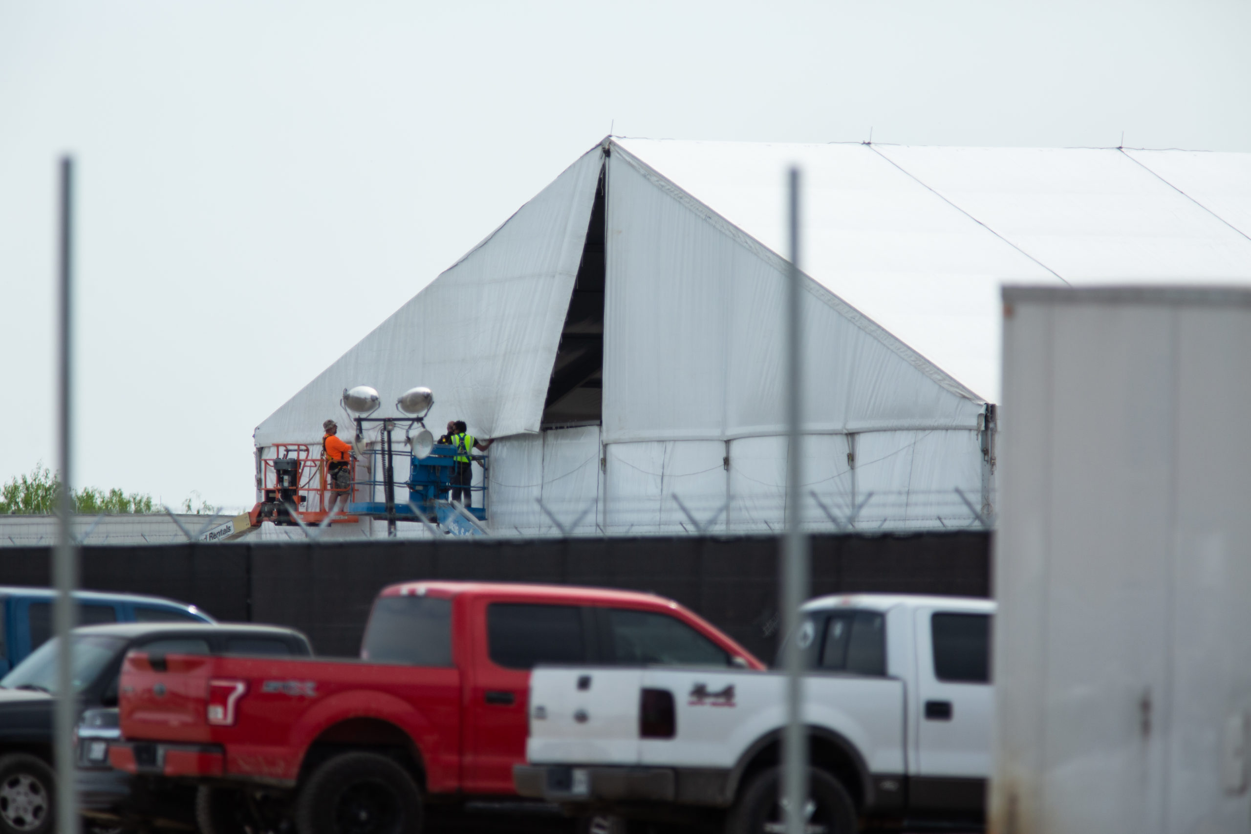 Contractors work to put up a plastic sheet on a soft-sided Customs and Border Protection migrant processing facility in Donna, Texas, on March 25, 2021. (Kaylee Greenlee - Daily Caller News Foundation)