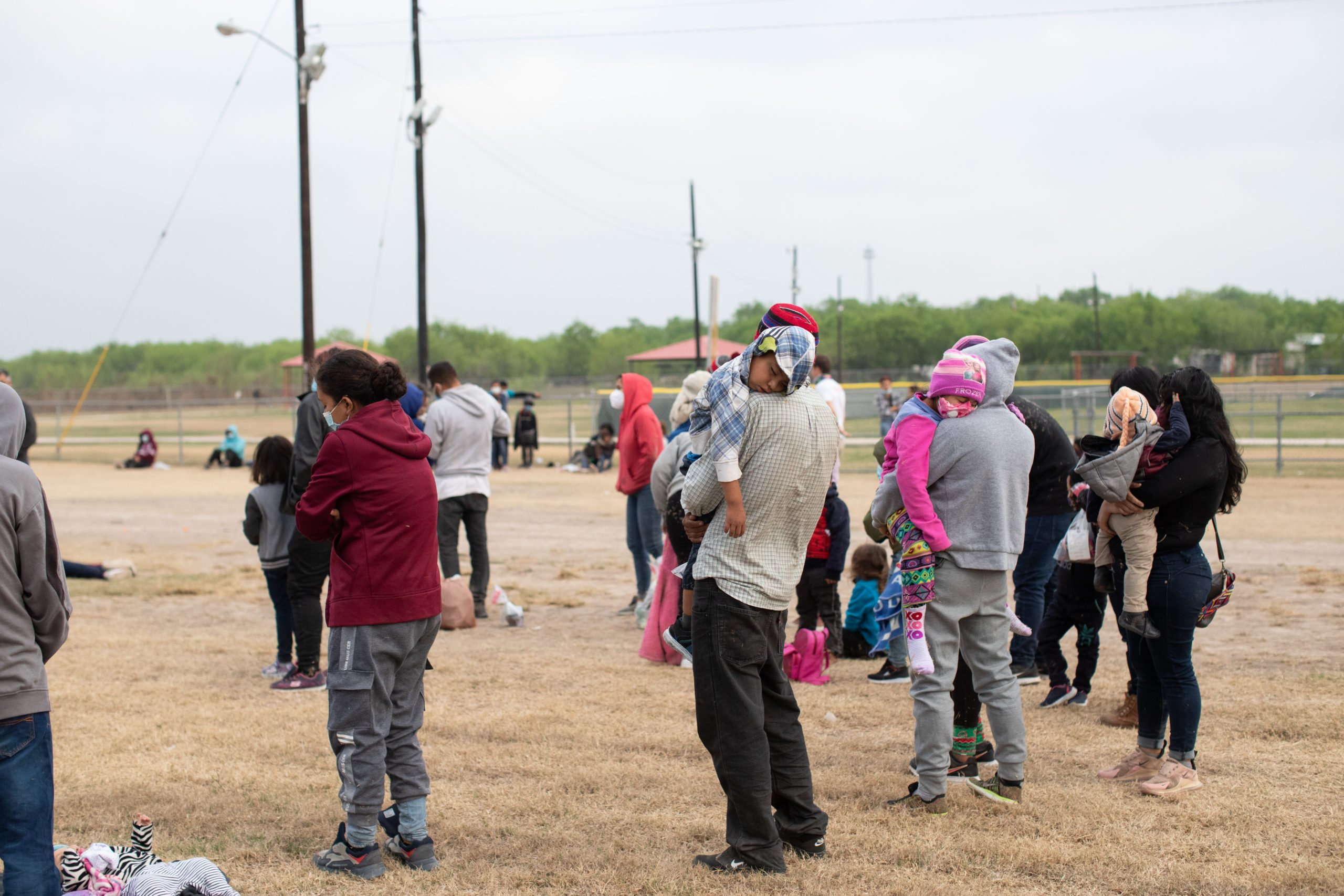 Several illegal migrants slept on the grass near the side of a public road as Customs and Border Protection officials worked to process the groups in La Joya, Texas on March 27, 2021. (Kaylee Greenlee - Daily Caller News Foundation)