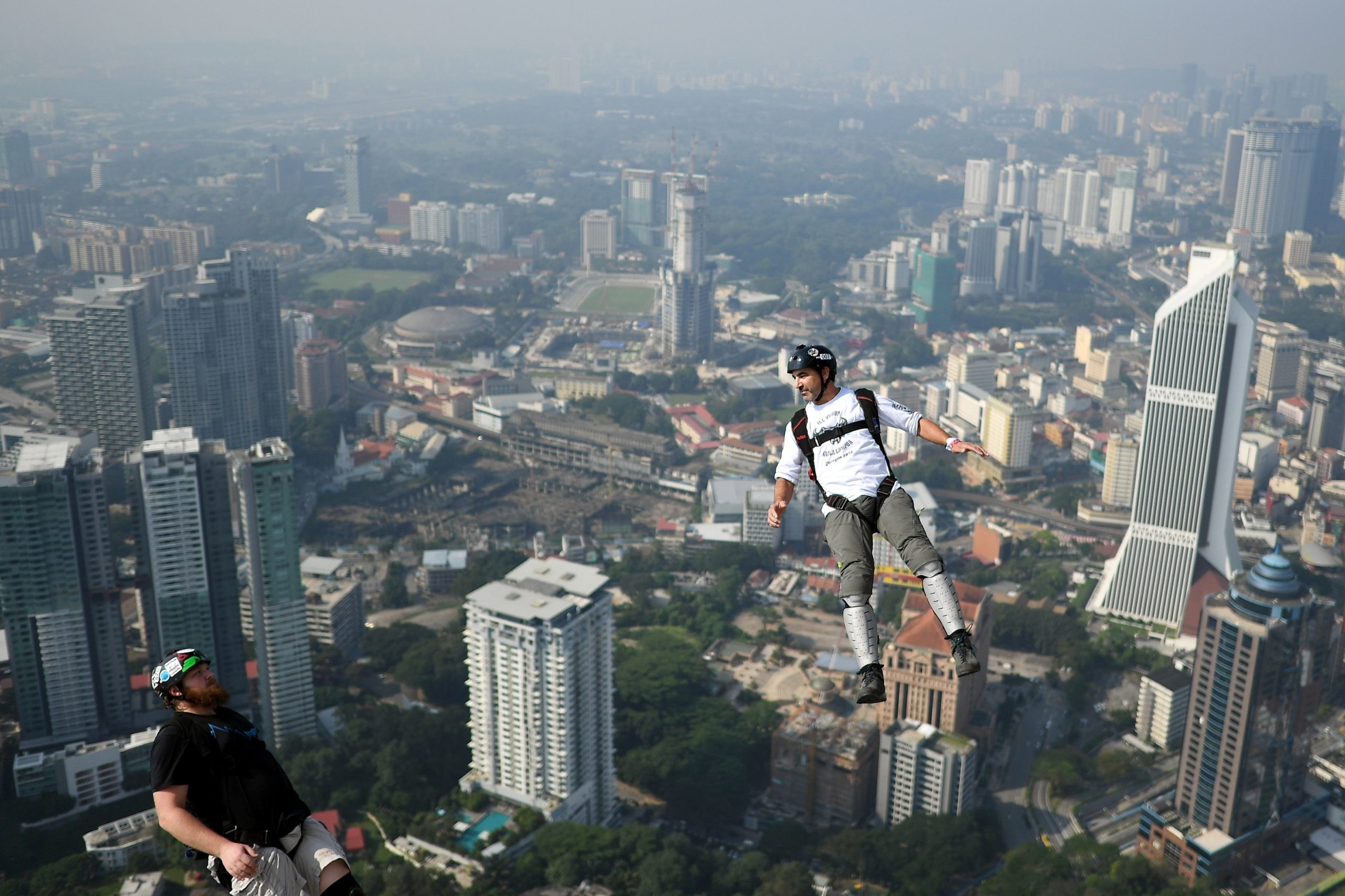 Base jumpers leap from the 300-metre high skydeck of Malaysia's landmark Kuala Lumpur Tower against the backdrop of the city's skyline in Kuala Lumpur on September 30, 2018 during the annual International KL Tower Base-Jump event. (Photo by Manan VATSYAYANA / AFP) (Photo credit should read MANAN VATSYAYANA/AFP via Getty Images)