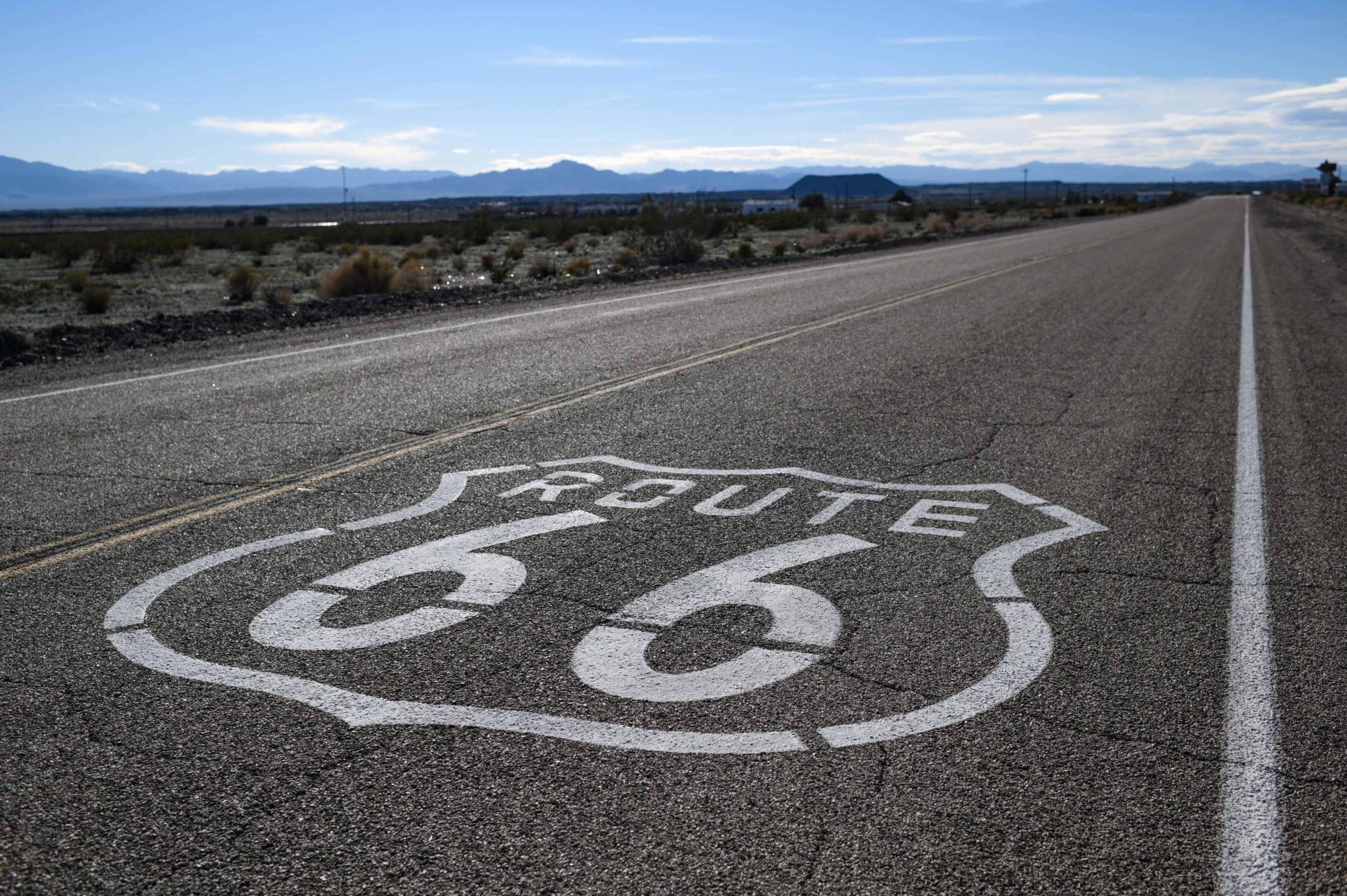 """A """"Route 66"""" sign is painted on the asphalt near Amboy in the Mojave Desert in California on February 27, 2019. - US.Route 66 (US 66 or Route 66), also known as the Will Rogers Highway, the Main Street of America or the Mother Road, was one of the original highways in the US Highway System. US 66 was established on November 11, 1926. The highway, which became one of the most famous roads in the United States, originally ran from Chicago, Illinois, through Missouri, Kansas, Oklahoma, Texas, New Mexico, and Arizona before ending in Santa Monica in Los Angeles County, California, covering a total of 2,448 miles (3,940 km). (Photo by Eric BARADAT / AFP) (Photo credit should read ERIC BARADAT/AFP via Getty Images)"""