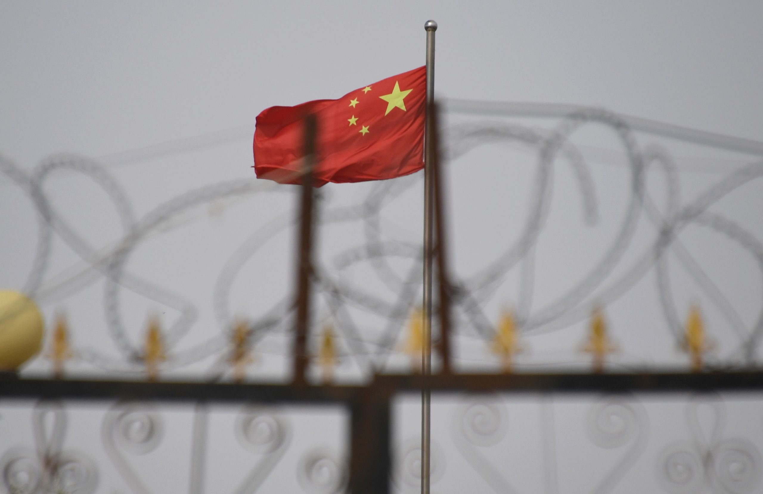 TOPSHOT - This photo taken on June 4, 2019 shows the Chinese flag behind razor wire at a housing compound in Yangisar, south of Kashgar, in China's western Xinjiang region. - A recurrence of the Urumqi riots which left nearly 200 people dead a decade ago is hard to imagine in today's Xinjiang, a Chinese region whose Uighur minority is straitjacketed by surveillance and mass detentions. A pervasive security apparatus has subdued the ethnic unrest that has long plagued the region. (Photo by GREG BAKER / AFP) (Photo by GREG BAKER/AFP via Getty Images)