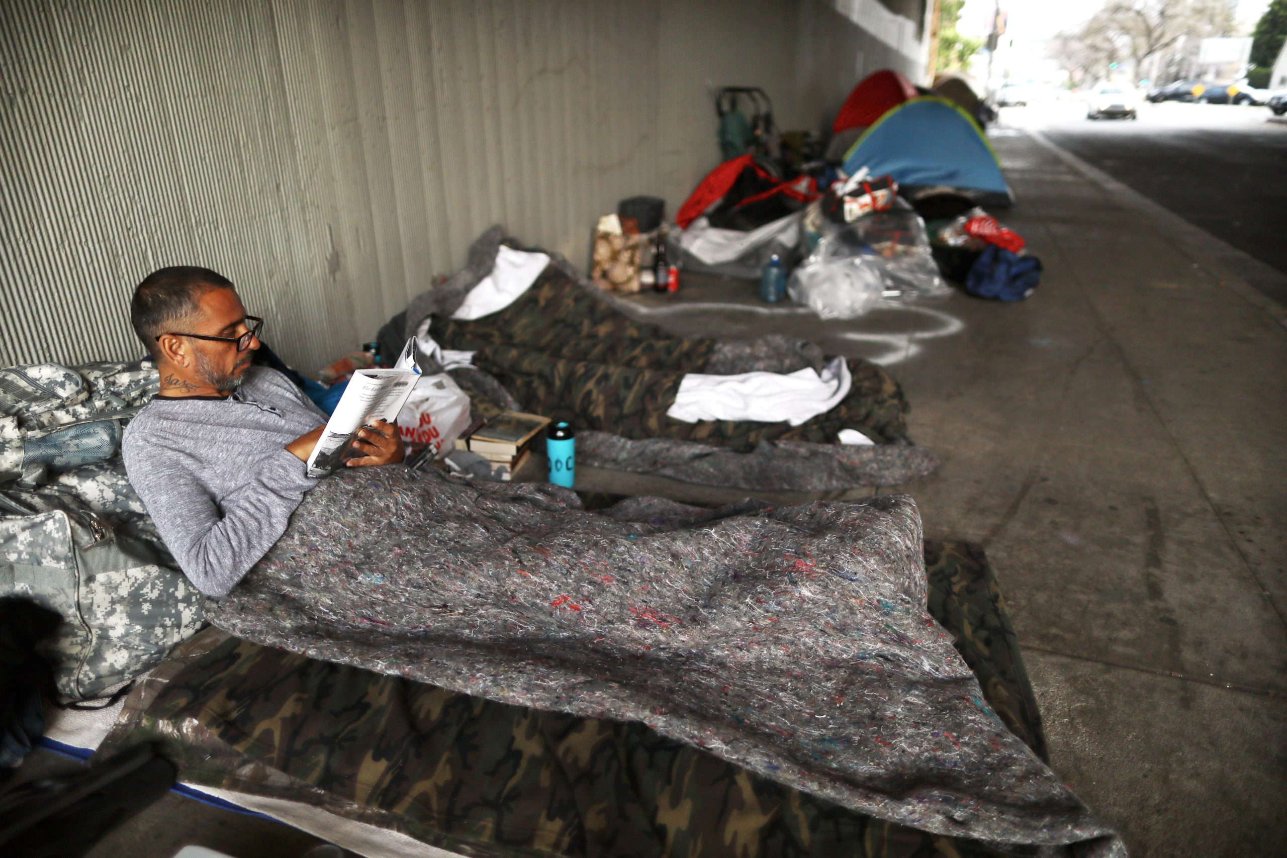 Travis Stanley, who said he has been homeless for three months and is a U.S. Navy veteran, reads on donated bedding where he normally sleeps beneath an overpass on June 5, 2019 in Los Angeles, California. The homeless population count in Los Angeles County leaped 12 percent in the past year to almost 59,000, according to officials. A lack of affordable housing in Los Angeles is the primary factor driving the spike in homelessness, according to Los Angeles Mayor Eric Garcetti. (Photo by Mario Tama/Getty Images)