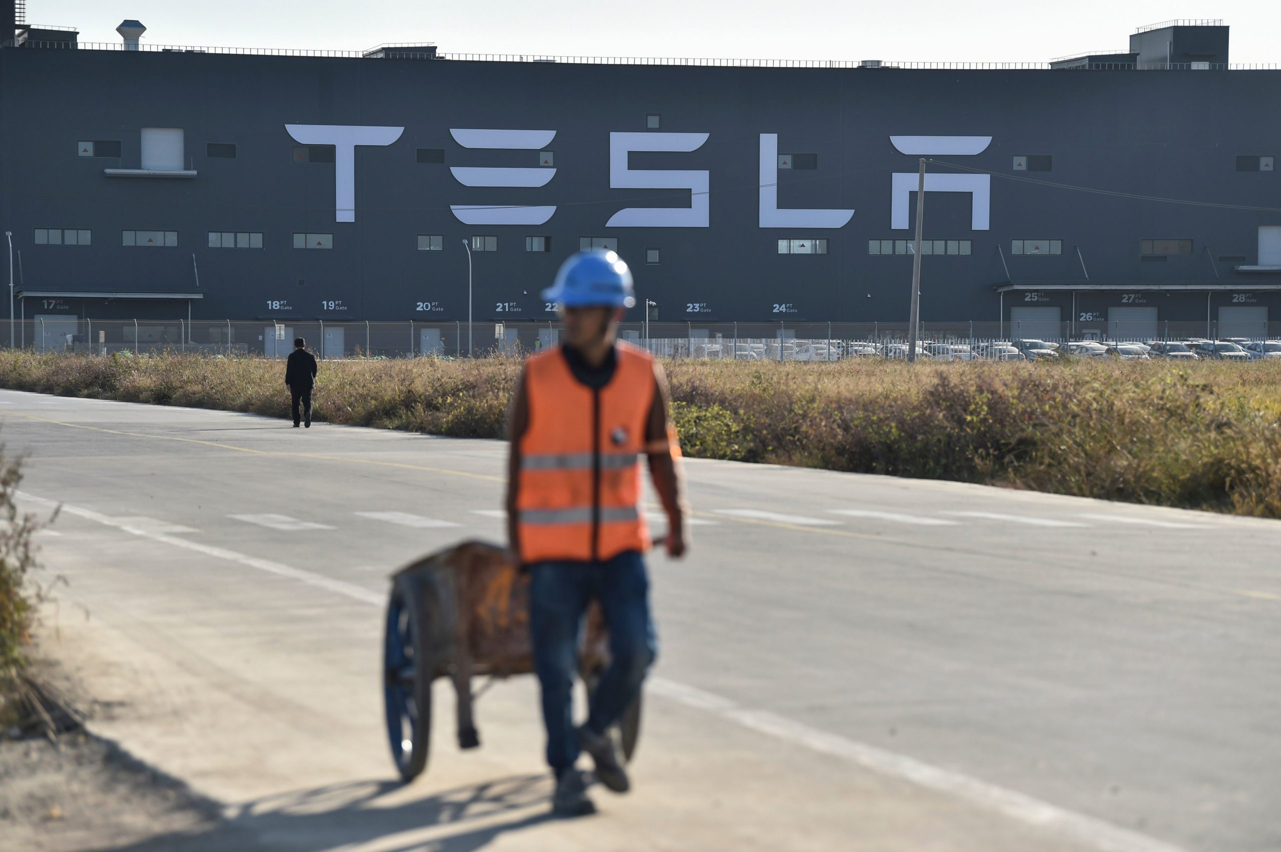 A worker walks on a road next to the new Tesla factory built in Shanghai, China on Nov. 8, 2019. (Hector Retamal/AFP via Getty Images)