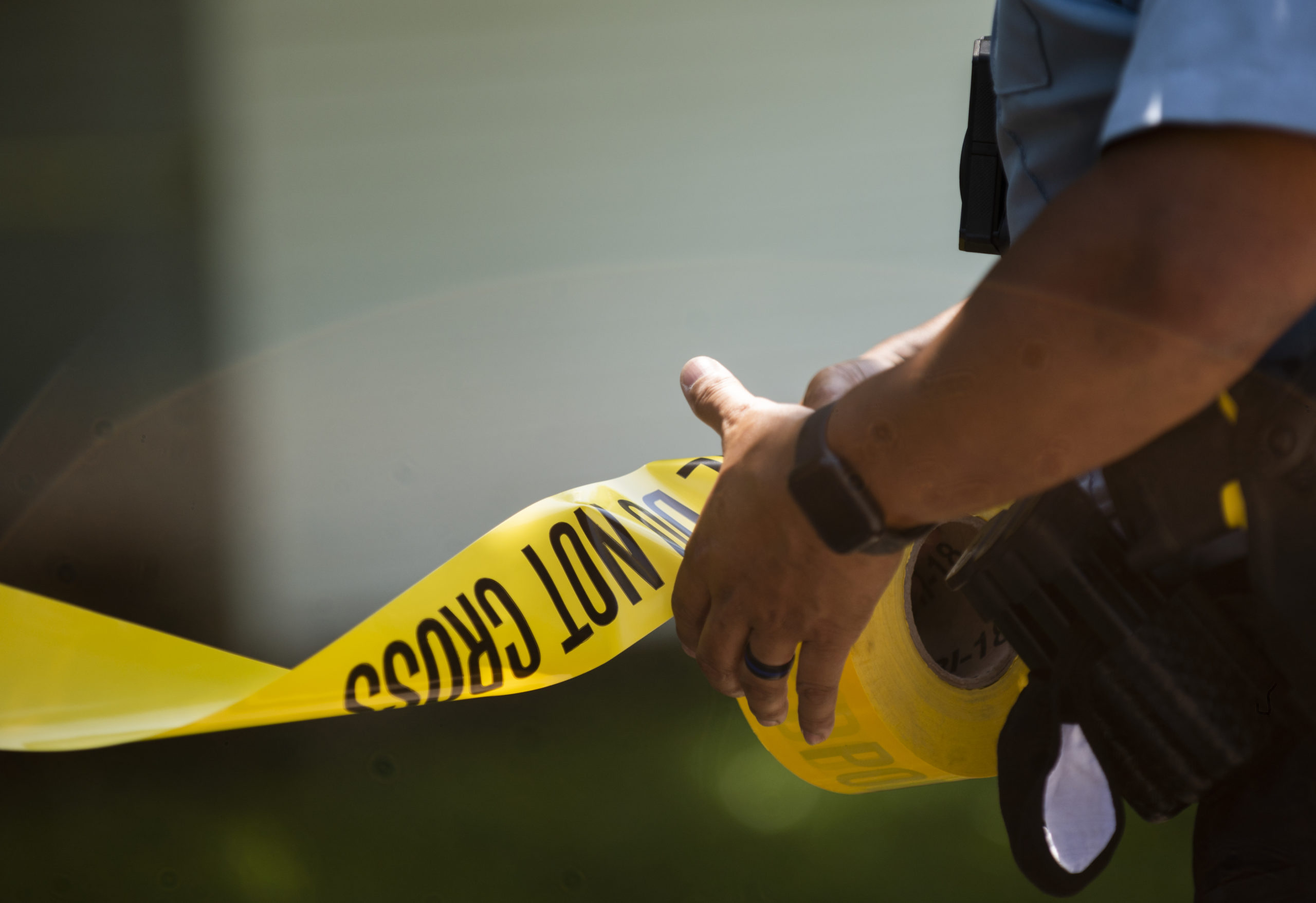 MINNEAPOLIS, MN - JUNE 16: A Minneapolis Police officers unrolls caution tape at a crime scene on June 16, 2020 in Minneapolis, Minnesota. The Minneapolis Police Department has been under increased scrutiny by residents and elected officials after the death of George Floyd in police custody on May 25. (Photo by Stephen Maturen/Getty Images)