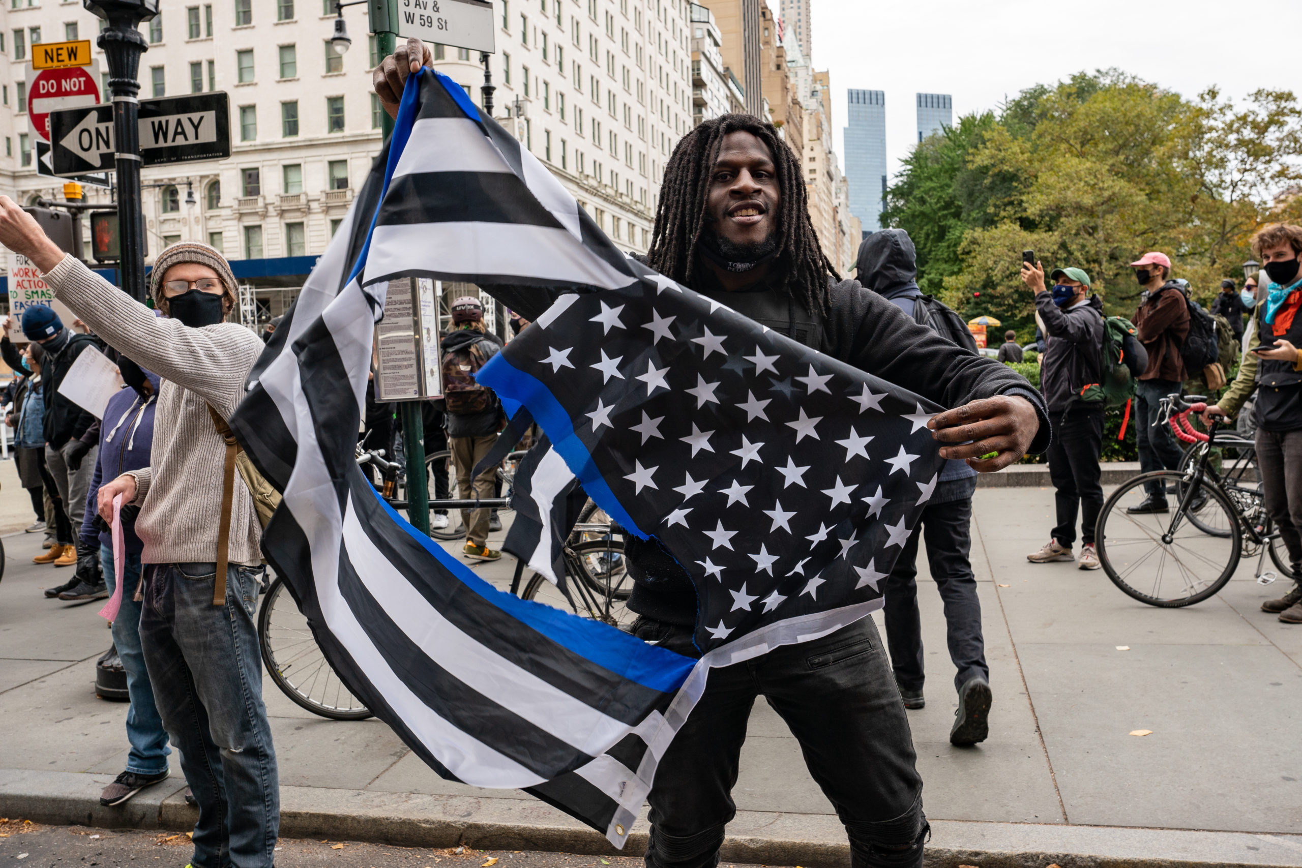 NEW YORK, NY - OCTOBER 25: A person holds a torn thin blue line American flag at a march and rally for President Donald Trump on 5th Avenue on October 25, 2020 in New York City. As the November 3rd presidential election nears, Trump supporters and protestors have taken to the streets to be heard. (Photo by David Dee Delgado/Getty Images)