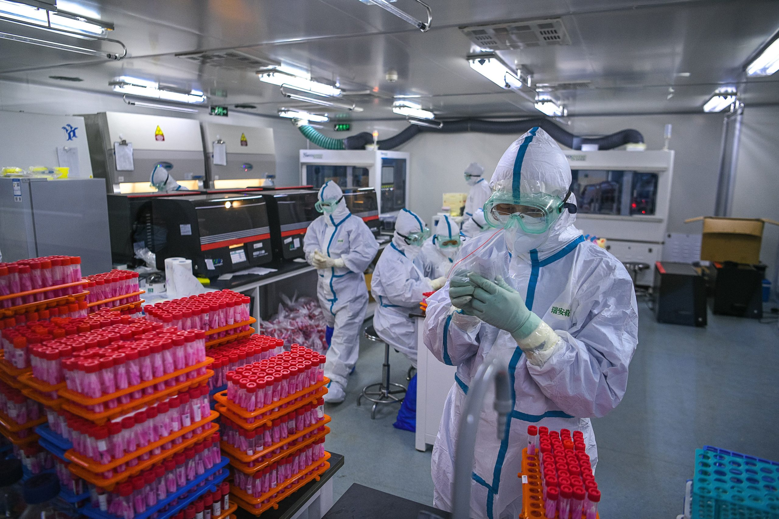 TOPSHOT - This photo taken on November 23, 2020 shows technicians processing Covid-19 coronavirus tests at a laboratory in Tianjin, China. (Photo by STR / CNS / AFP) / China OUT (Photo by STR/CNS/AFP via Getty Images)