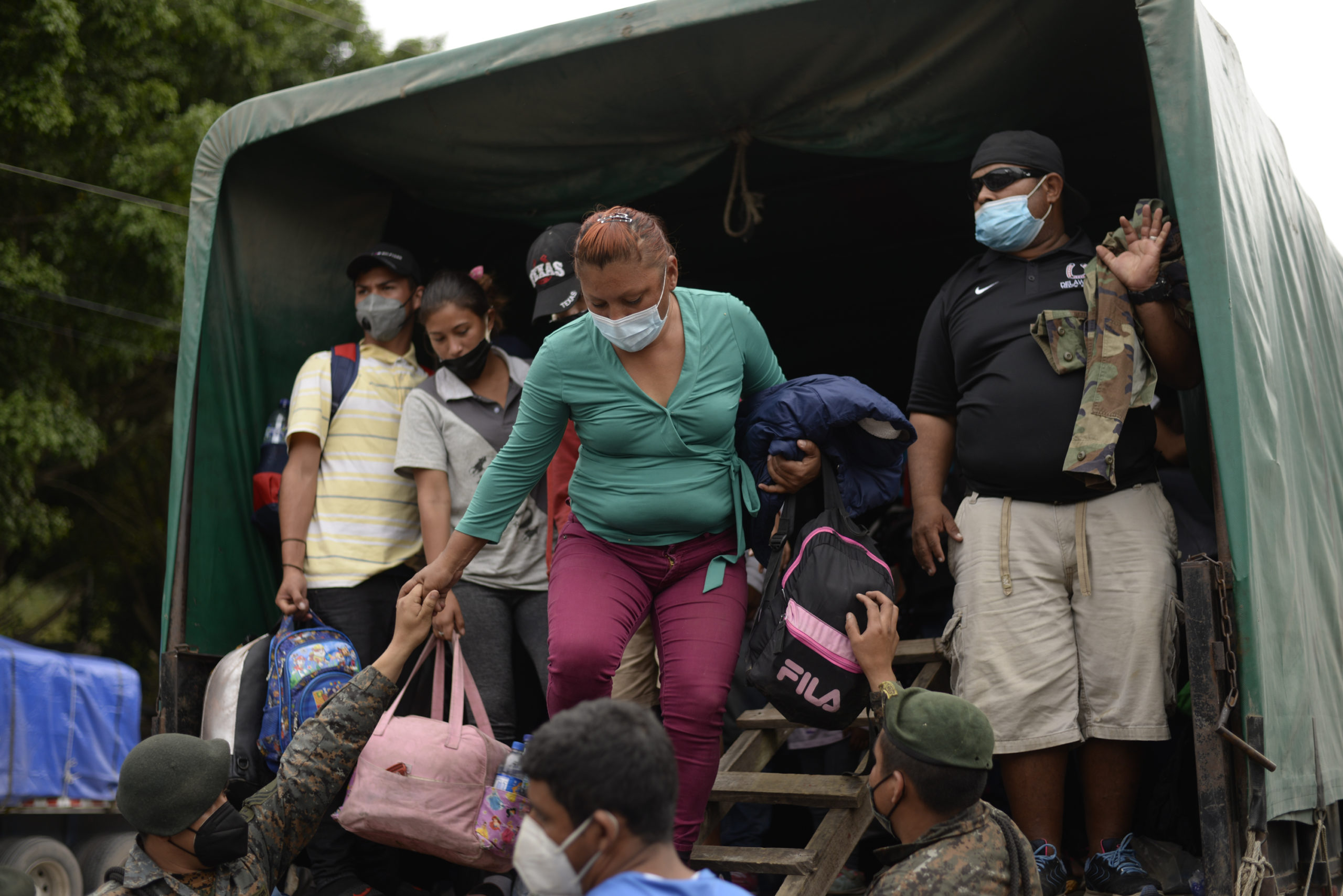 Honduran migrants who were part of a U.S.-bound caravan are helped getting out of a truck in Guatemala on Jan. 19. (Johan Ordonez/AFP via Getty Images)