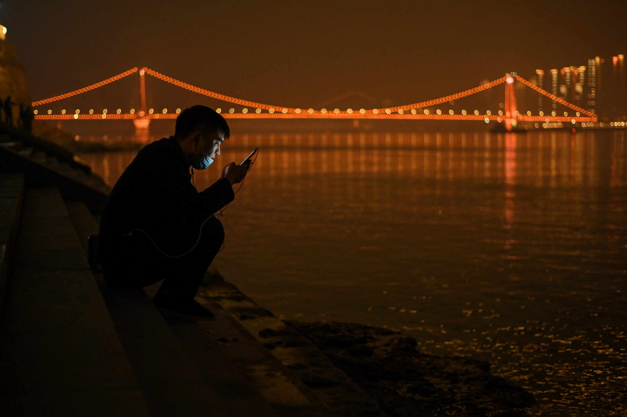 TOPSHOT - A man looks at his mobile phone as he sits on the banks of the Yangtze River in Wuhan in China's central Hubei province on February 11, 2021, ahead of the start of the Lunar New Year, which ushers in the Year of the Ox on February 12. (Photo by Hector RETAMAL / AFP) (Photo by HECTOR RETAMAL/AFP via Getty Images)