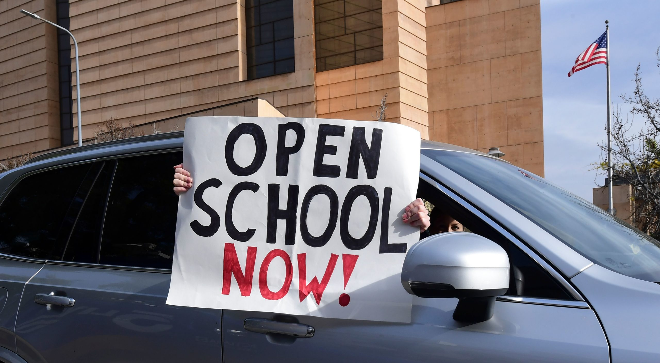 """Signs calling for schools to reopen are displayed by people in passing vehicles during an """"Open Schools Now"""" rally via car caravan by supporters of The Students First Coalition of Los Angeles on February 15, 2021 in Los Angeles, California. (Photo by FREDERIC J. BROWN/AFP via Getty Images)"""