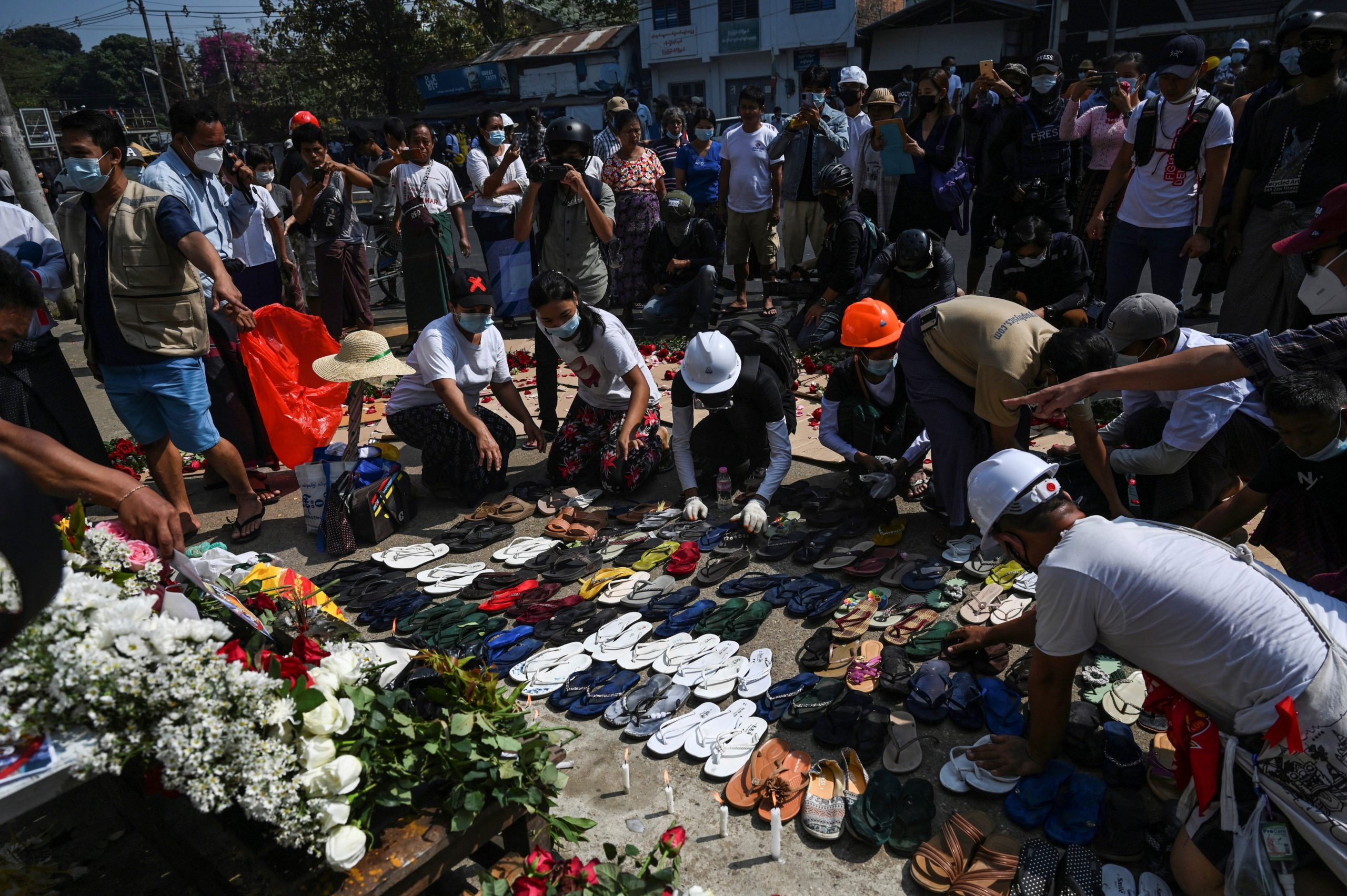 Protesters arrange abandoned flip flops and other belongings next to a makeshift altar for teacher Tin Nwe Yi left behind during a crackdown in Yangon on March 1, 2021 after she was killed during a demonstration against the military coup. (Photo by STR / AFP) (Photo by STR/AFP via Getty Images)