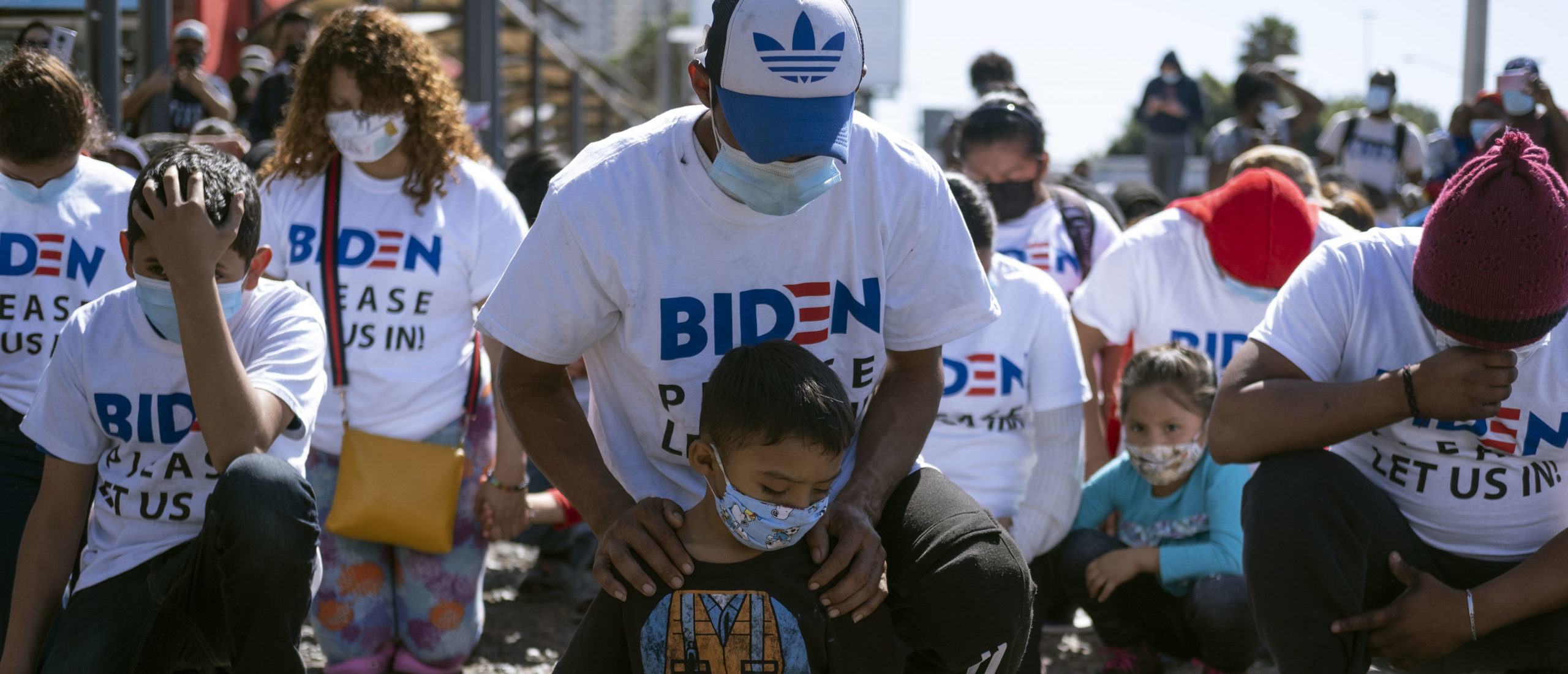 TOPSHOT - Yadiel Garcia and his father Fabricio, from Honduras, kneel as they pray during a migrant demonstration demanding clearer United States migration policies, at San Ysidro crossing port in Tijuana, Baja California state, Mexico on March 2, 2021. - Thousands of migrants out of the Migrant Protection Protocol (MPP) program are stranded along the US-Mexico border without knowing when or how they will be able to start their migratory process with US authorities. (Photo by Guillermo Arias / AFP) (Photo by GUILLERMO ARIAS/AFP via Getty Images)
