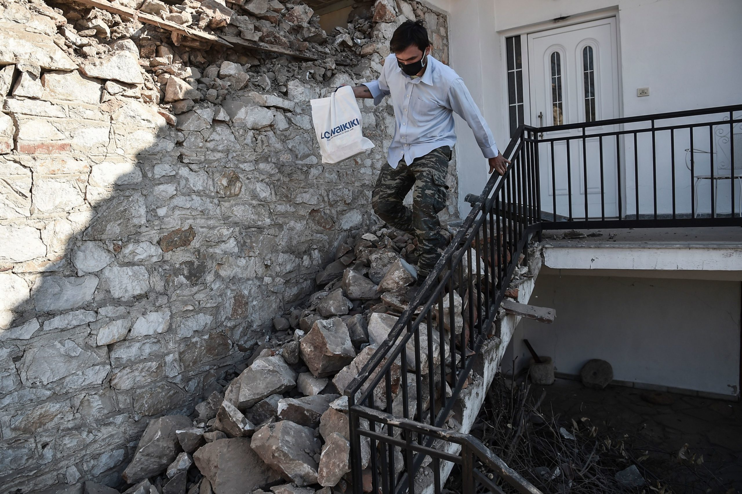A man carries his belongings from a damaged house in the village of Damasi, near the town of Tyrnavos, after a strong 6,3-magnitude earthquake hit the Greek central region of Thessaly. - A strong 6.3-magnitude earthquake hit central Greece on March 3, damaging several buildings, including schools, and prompting residents near the epicentre to rush into the streets. According to the Athens observatory, the epicentre of the quake was 21 kilometres (13 miles) south of the town of Elassona, near Larissa and was eight kilometres deep. (Photo by Sakis MITROLIDIS / AFP) (Photo by SAKIS MITROLIDIS/AFP via Getty Images)