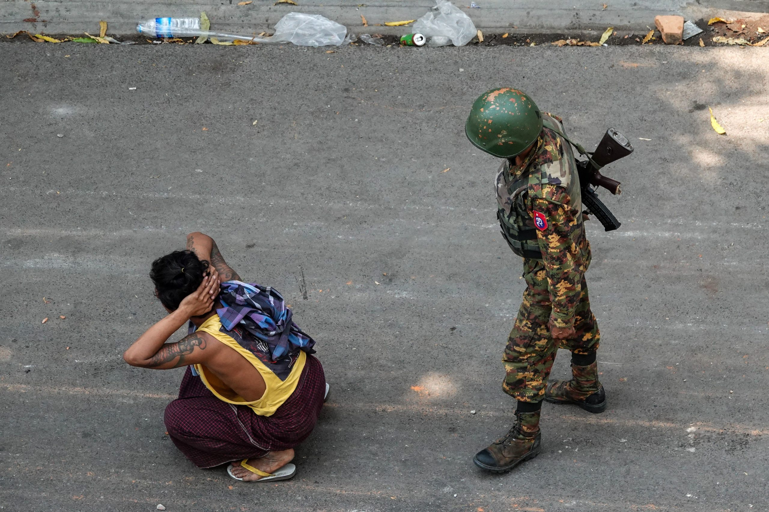 TOPSHOT - A soldier stands next to a detained man during a demonstration against the military coup in Mandalay on March 3, 2021. (Photo by STR / AFP) (Photo by STR/AFP via Getty Images)