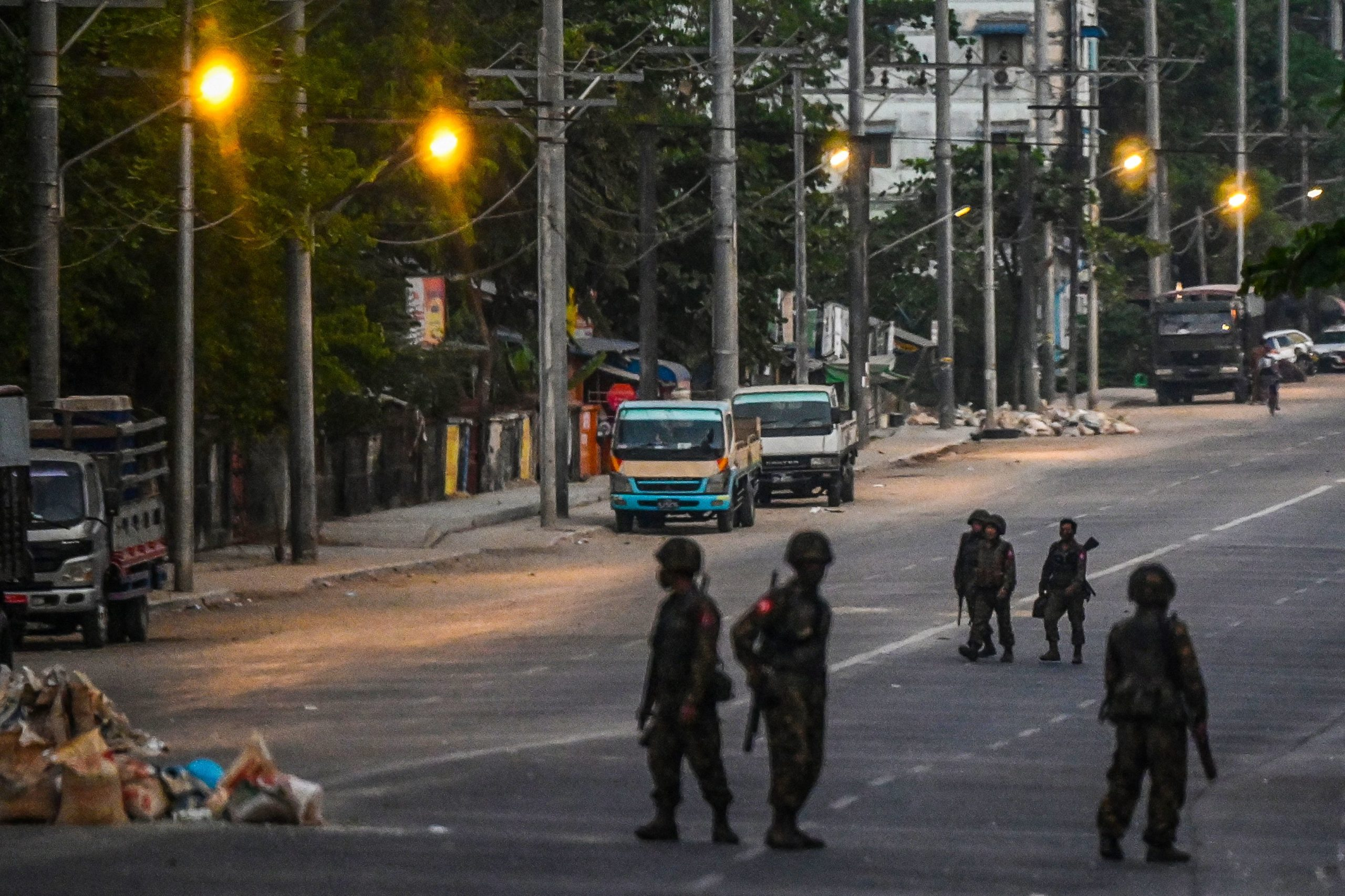 Soldiers keep watch as they block an empty street in Yangon on March 10, 2021, as security forces continue to crackdown on demonstrations by protesters against the military coup. (Photo by STR / AFP) (Photo by STR/AFP via Getty Images)